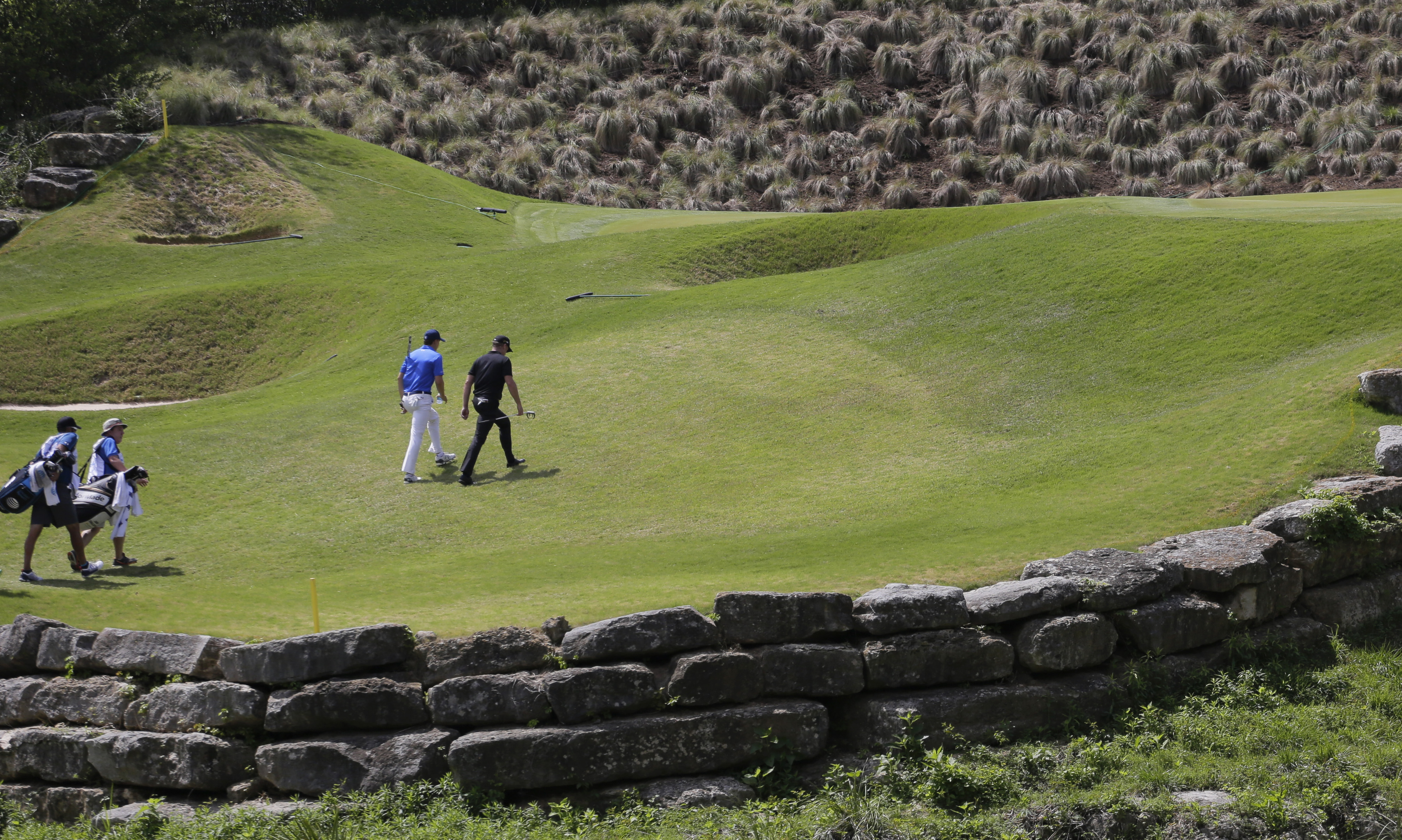 Jamie Donaldson of Wales, right, and Jordan Spieth, second from right, walk on the fairway on the fourth hole during round-robin play at the Dell Match Play Championship golf tournament at Austin County Club, Wednesday, March 23, 2016, in Austin, Texas. (