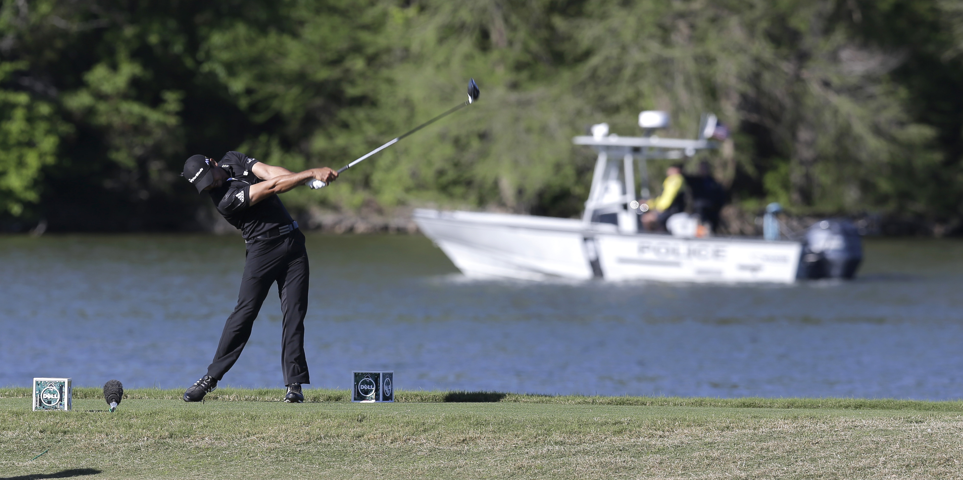 Jason Day, of Australia, hits his tee shot on the 14th hole as a boat passes on Lake Austin during round-robin play against Thongchai Jaidee at the Dell Match Play Championship golf tournament at Austin County Club, Thursday, March 24, 2016, in Austin, Te