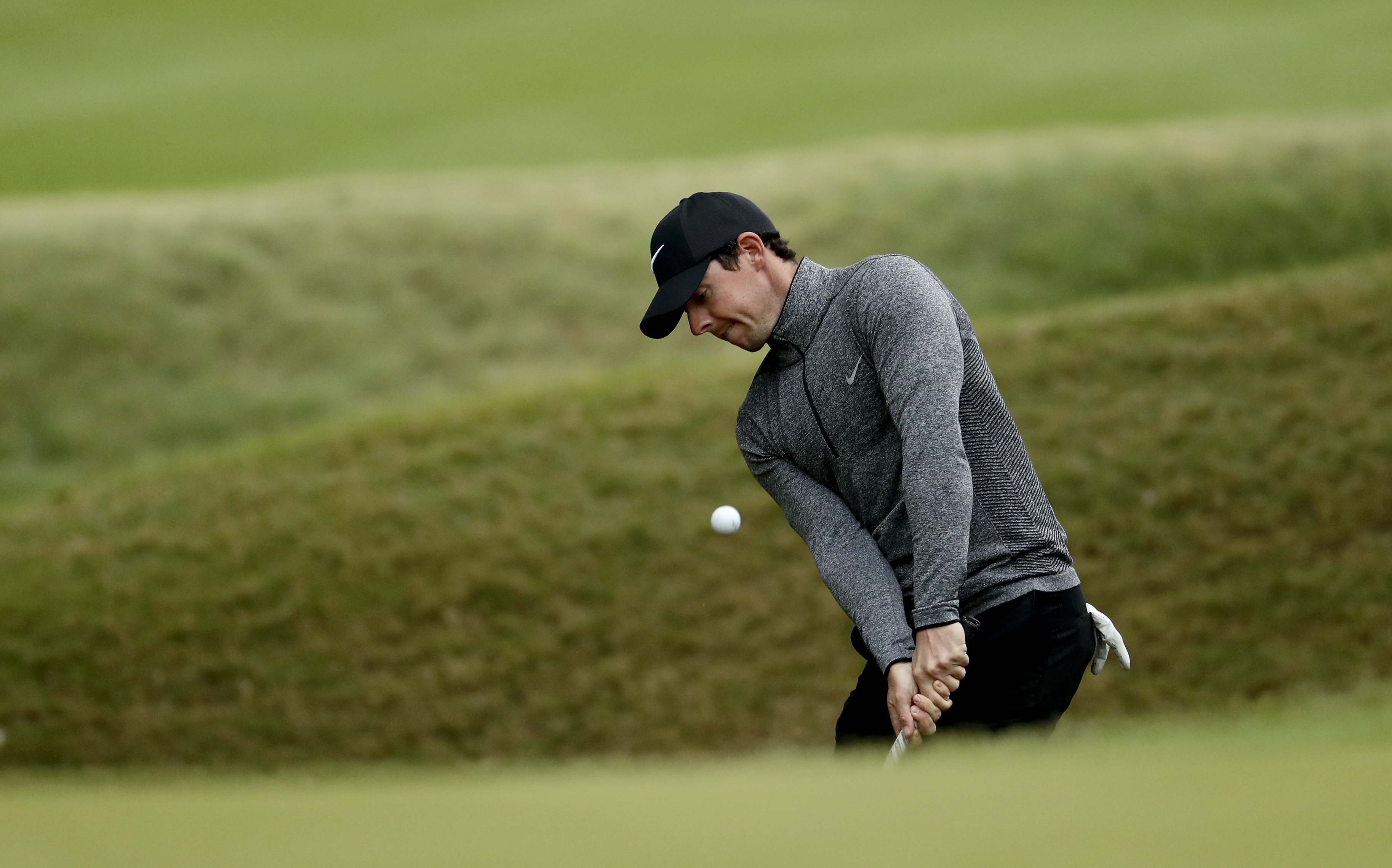 Rory McIlroy, of Northern Ireland, chips onto the sixth green during the round of 16 play against Dustin Johnson at the Dell Match Play Championship golf tournament at Austin County Club Saturday, March 26, 2016, in Austin, Texas. (AP Photo/Charlie Riedel