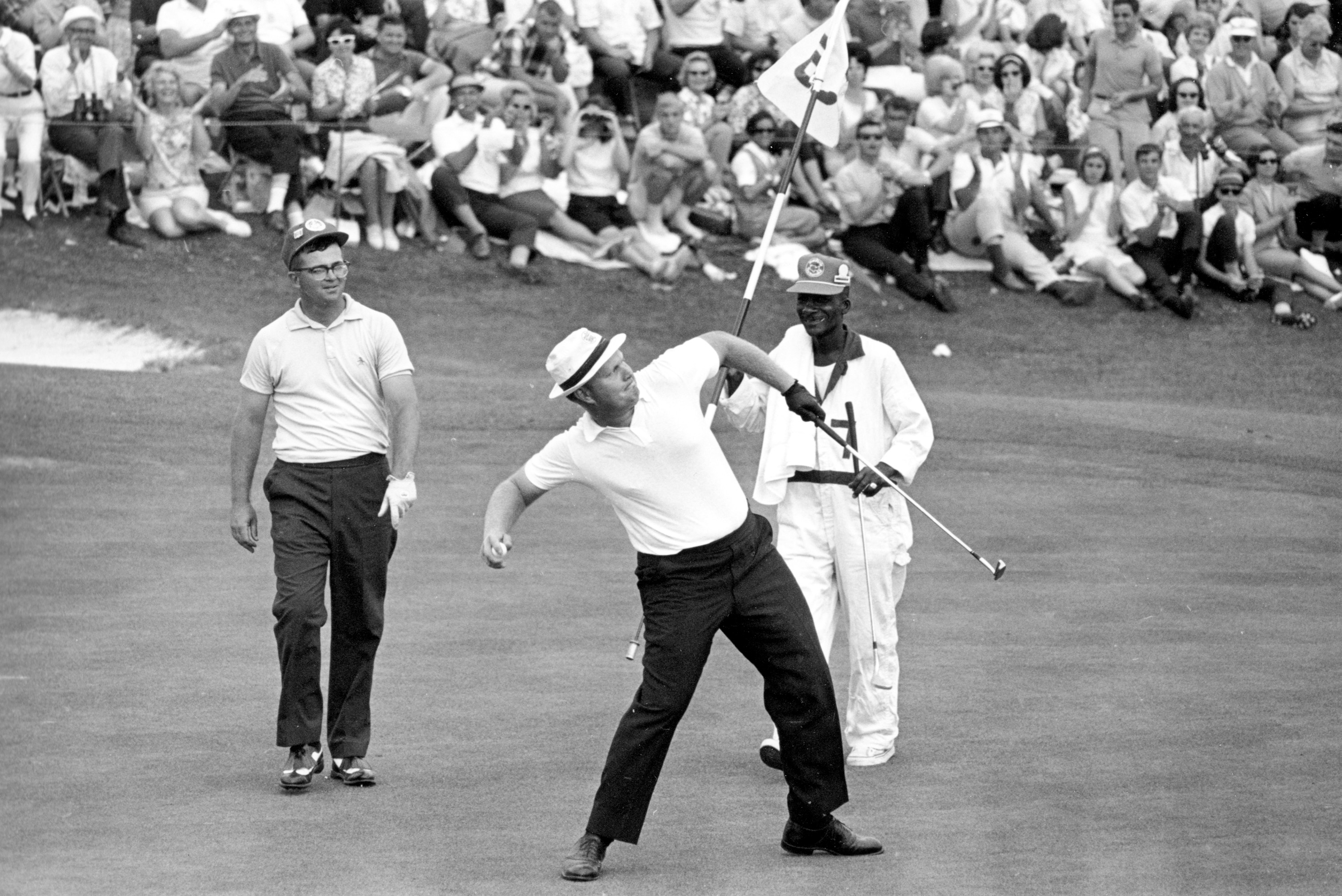 FILE - In this April 11, 1965 file photo, Jack Nicklaus prepares to toss his ball down the fairway after he putted out to win the Masters Championship at Augusta National Golf Club in Augusta, Ga. Nicklaus was tied with Gary Player and Arnold Palmer after