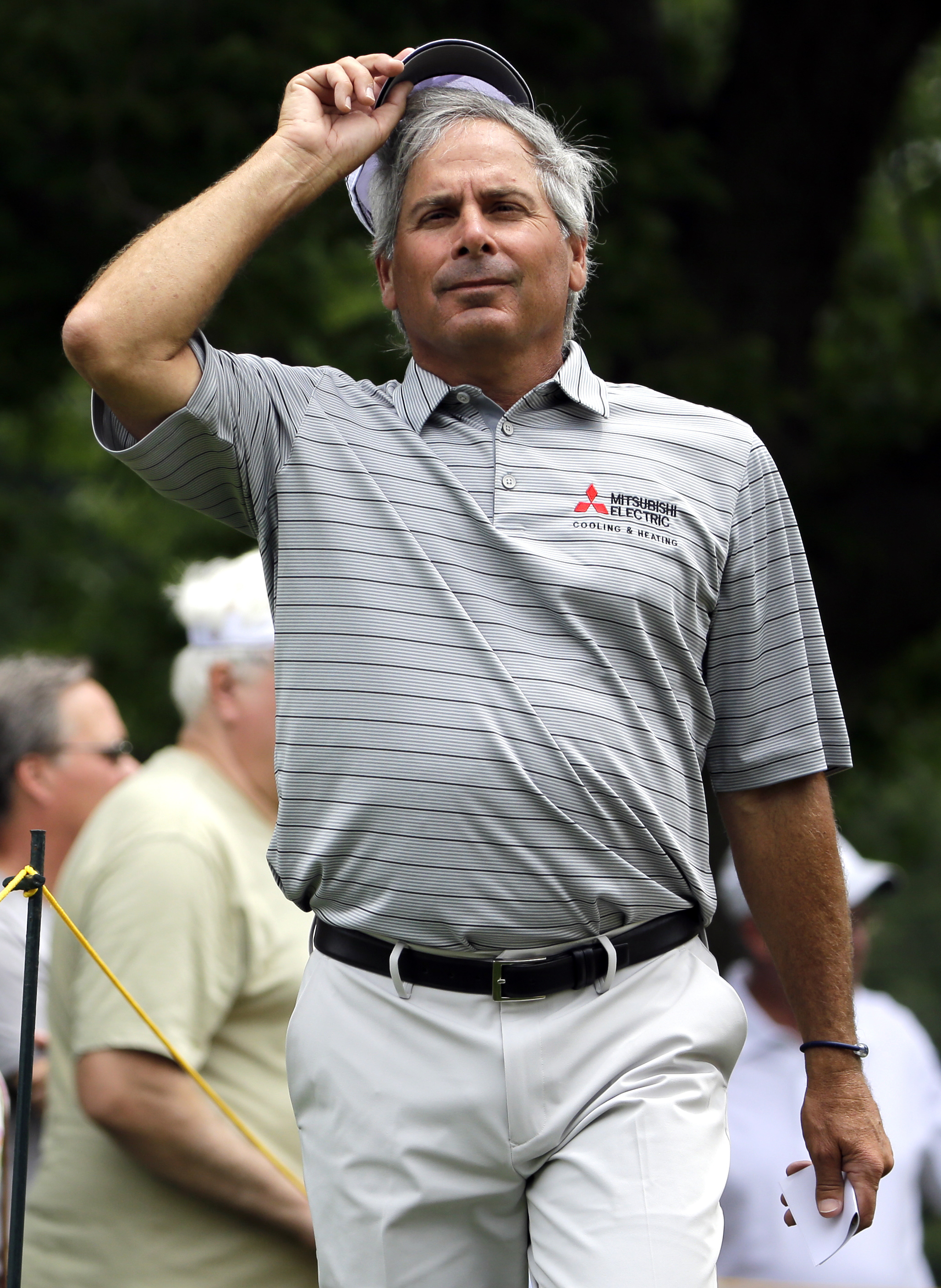 Fred Couples adjusts his cap as he walks to the third hole from the second green during the second round of the Encompass Championship golf tournament Saturday, July 11, 2015, in Glenview, Ill. (AP Photo/Nam Y. Huh)