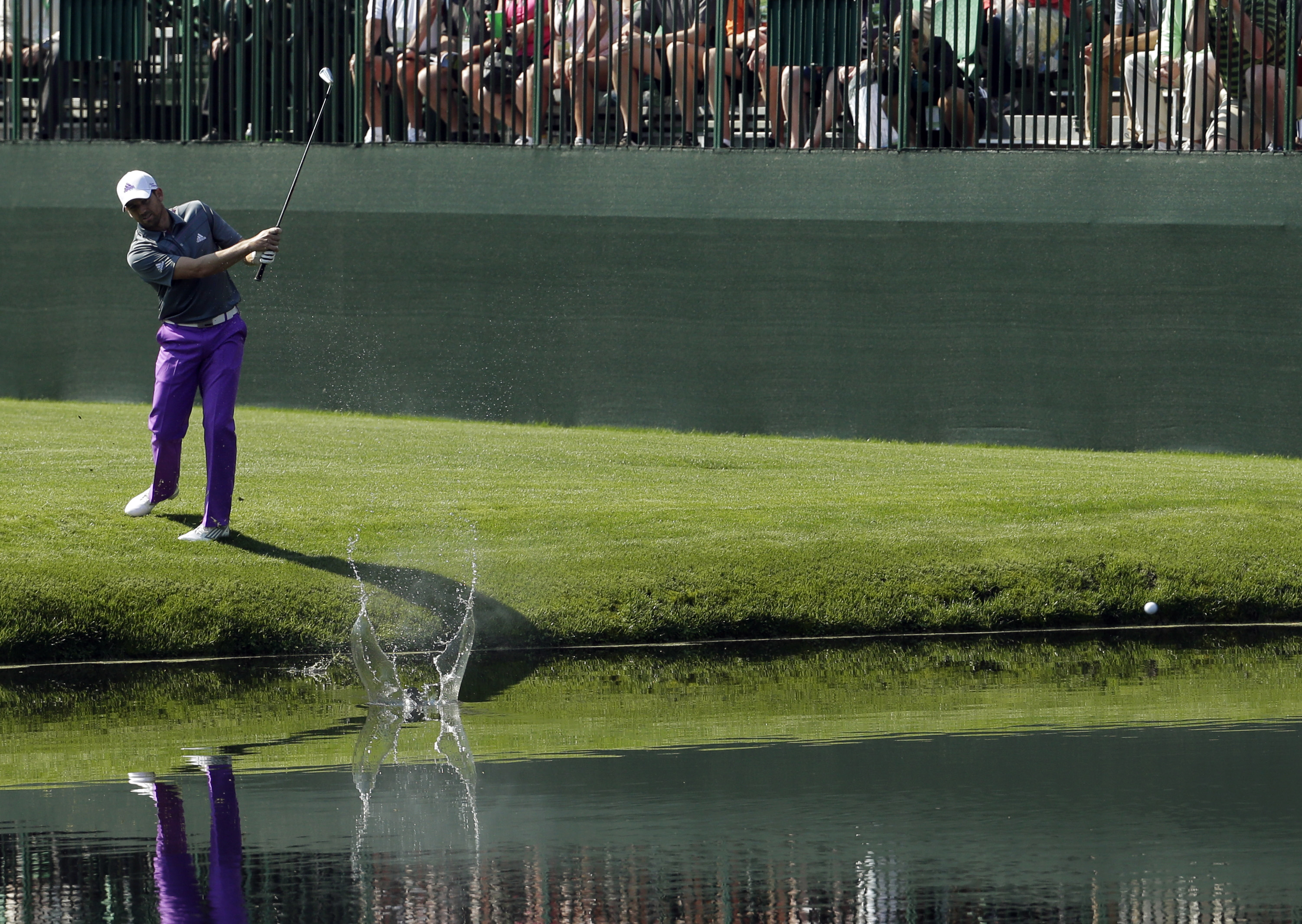 FILE - In this April 9, 2014, file photo, Sergio Garcia, of Spain, skips a ball across the water on the 16th hole during a practice round for the Masters golf tournament in Augusta, Ga. For many, the 16th hole is the place to be before the first major of