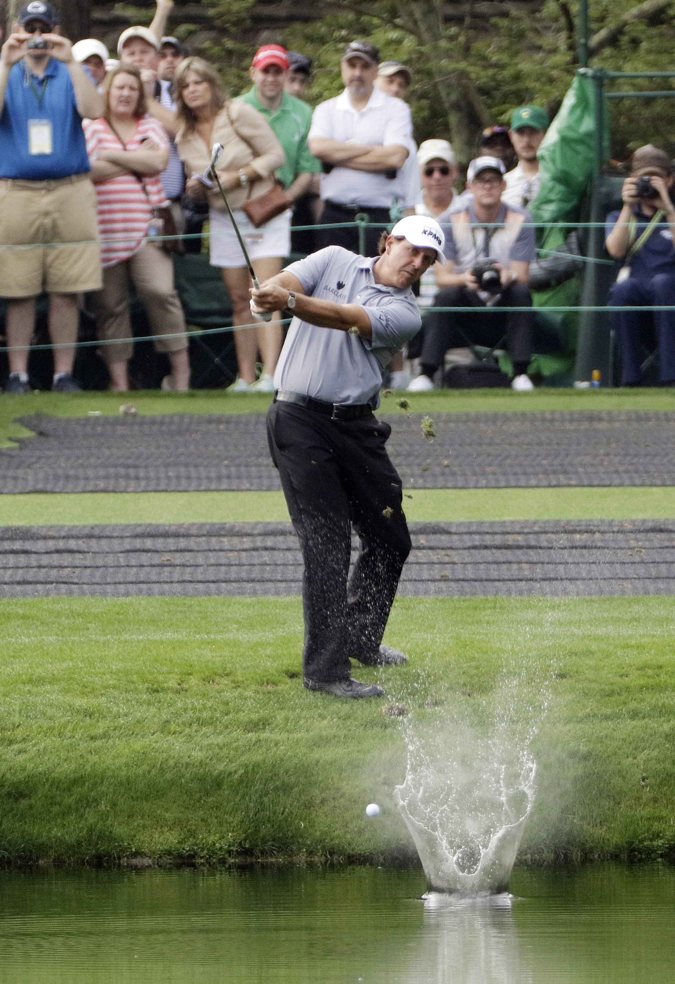 FILE - In this April 8, 2015, file photo, Phil Mickelson skips a ball across the water hole on the 16th fairway during a practice round for the Masters golf tournament in Augusta, Ga. For many, the 16th hole is the place to be before the first major of th