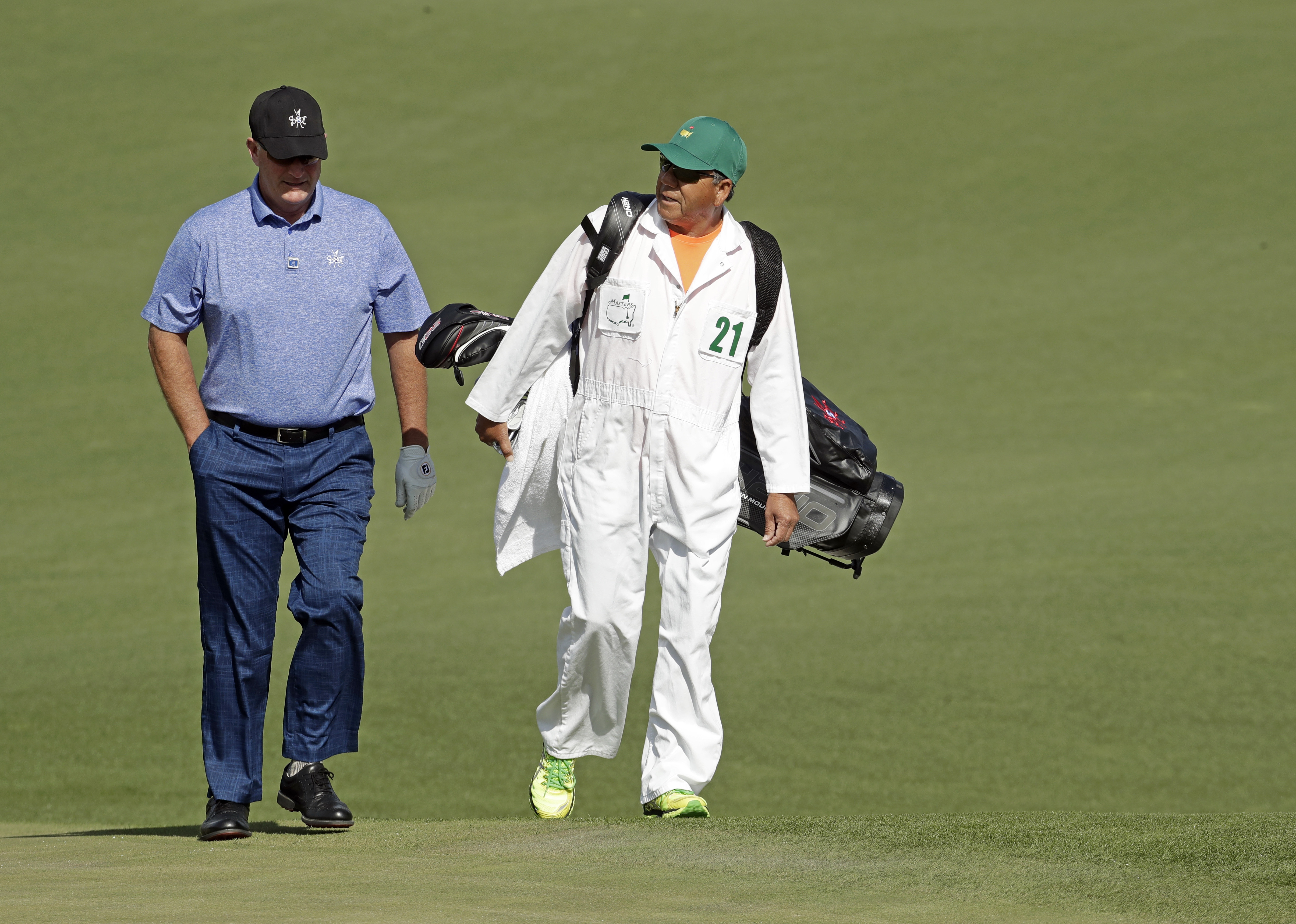 Caddie Eseban Tolledo walks with Sandy Lyle, of Scotland, on the second hole during a practice round for the Masters golf tournament Wednesday, April 6, 2016, in Augusta, Ga. (AP Photo/Charlie Riedel)