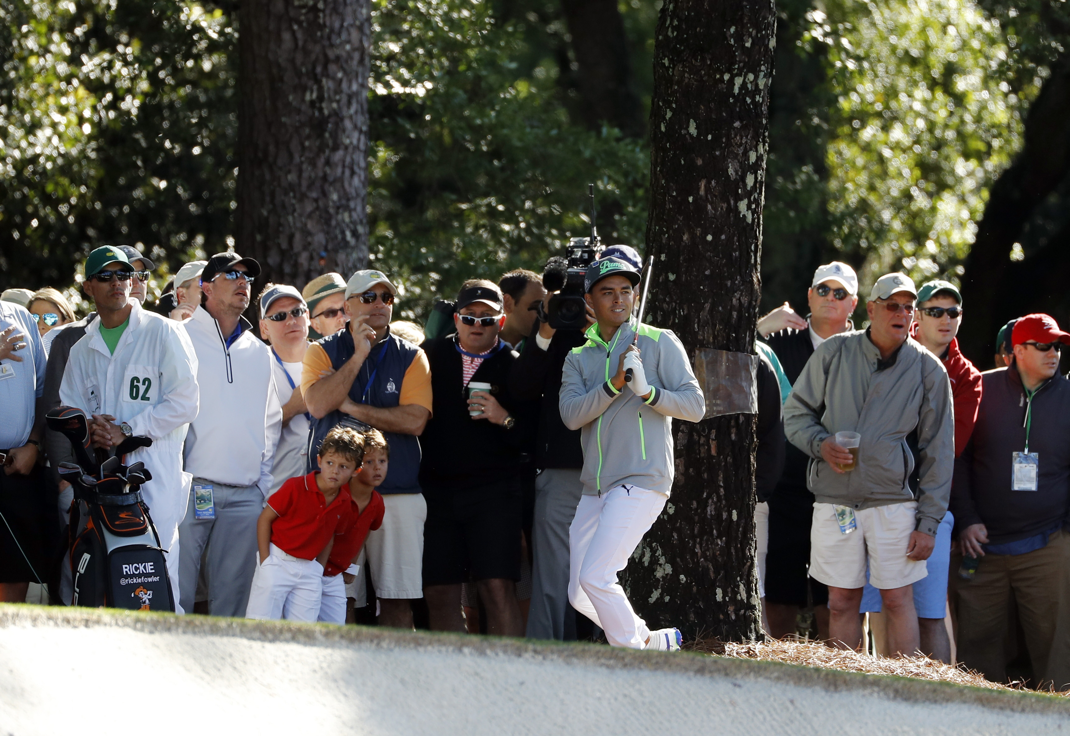 Rickie Fowler watches as he shot bounces off a tree on the first fairway during the first round of the Masters golf tournament Thursday, April 7, 2016, in Augusta, Ga. (AP Photo/Matt Slocum)