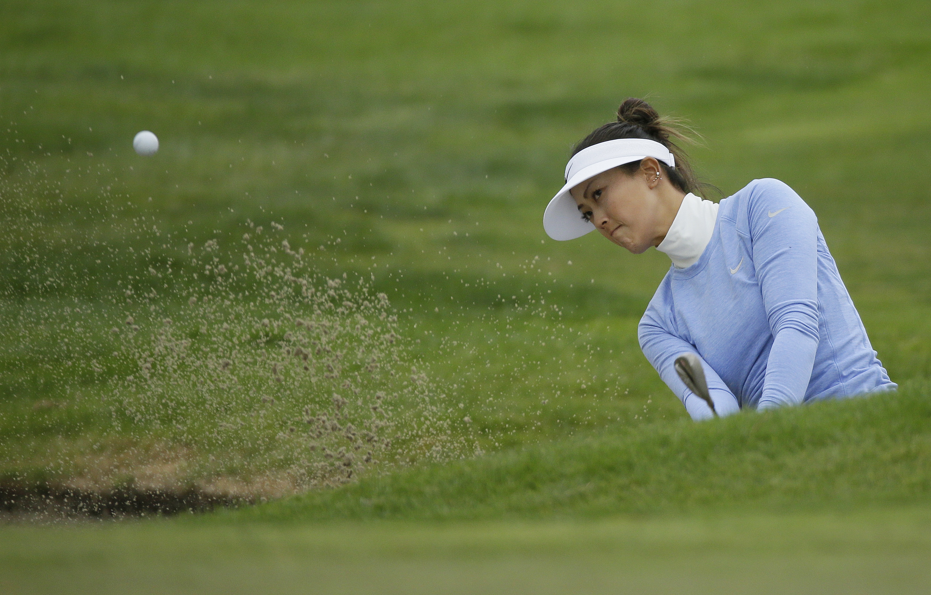 Michelle Wie hits out of a bunker up to the sixth green of the Lake Merced Golf Club during the second round of the Swinging Skirts LPGA Classic golf tournament Friday, April 22, 2016, in Daly City, Calif. (AP Photo/Eric Risberg)