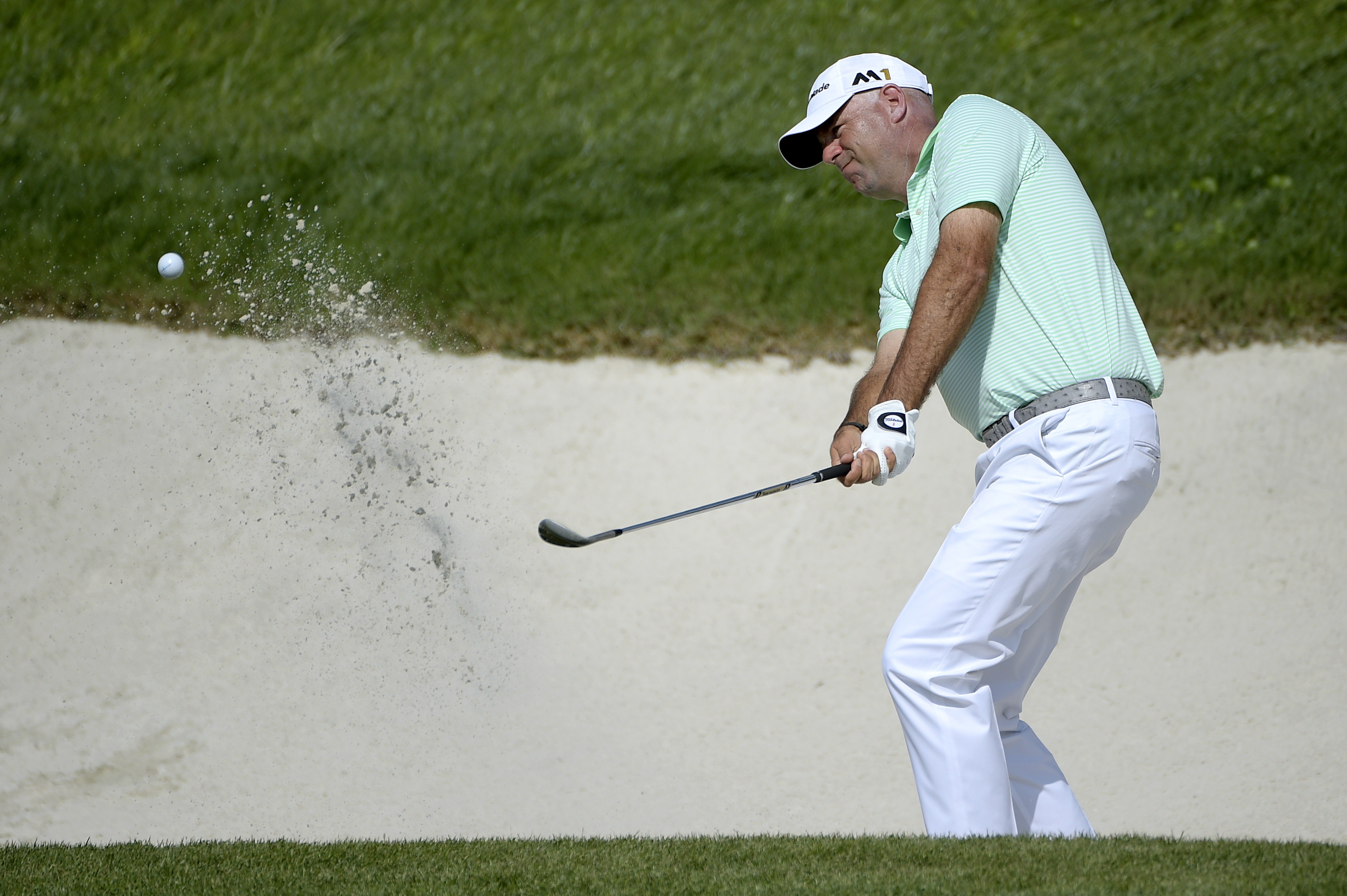 Stewart Cink hits out of a bunker onto the 18th green during the first round of the Arnold Palmer Invitational golf tournament in Orlando, Fla., Thursday, March 17, 2016. (AP Photo/Phelan M. Ebenhack)