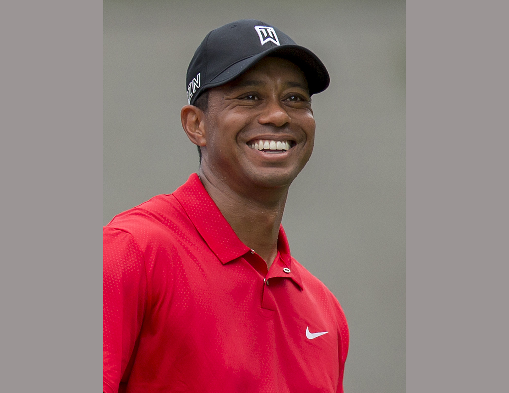 FILE - In this Aug. 23, 2015 file photo, Tiger Woods smiles at the third tee during the final round of the Wyndham Championship golf tournament in Greensboro, N.C. Woods is writing his first book since 2001 that is due out next spring. The book does not h