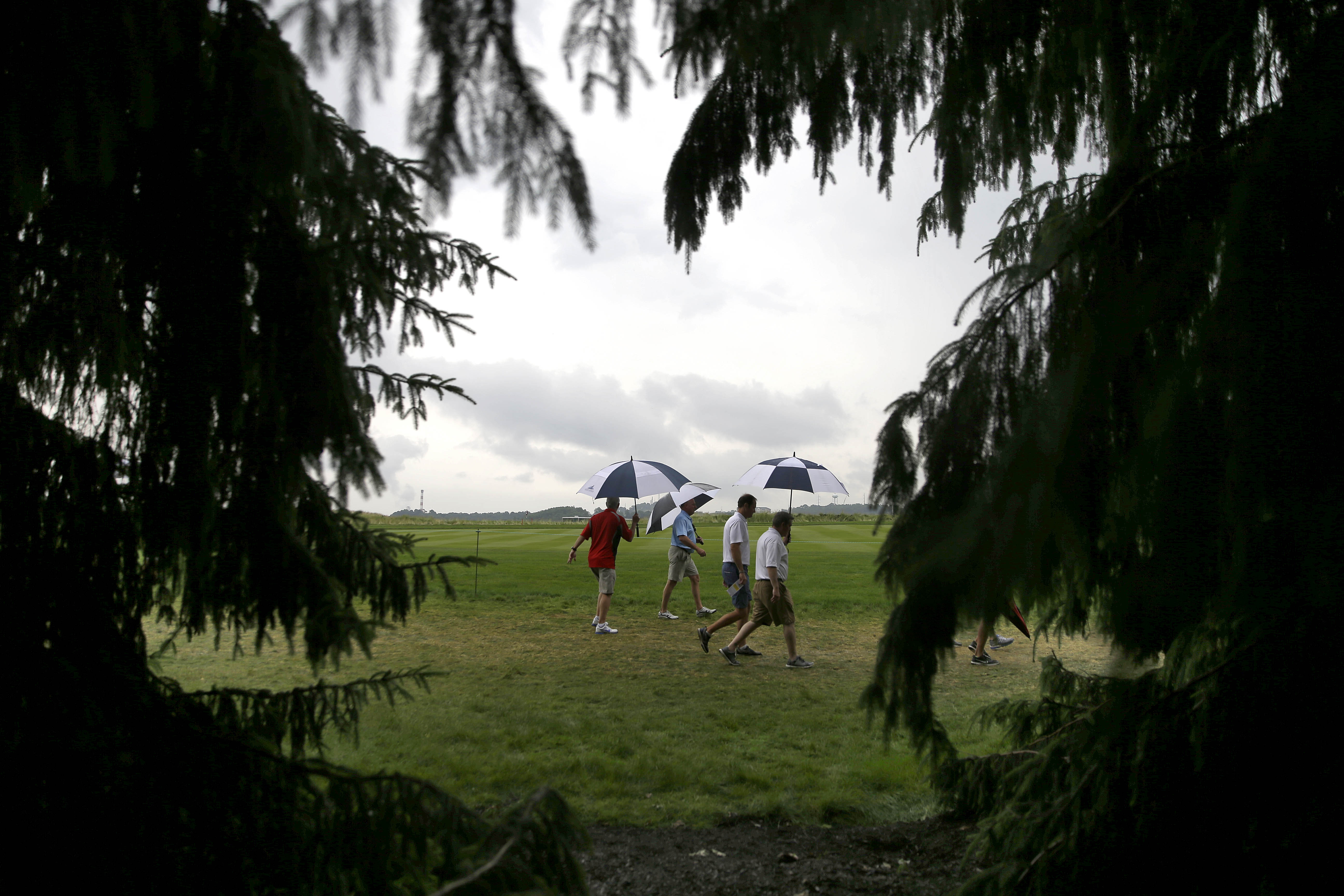 Fans leaves the course after play was suspended during the first round of the U.S. Open golf championship at Oakmont Country Club on Thursday, June 16, 2016, in Oakmont, Pa. (AP Photo/John Minchillo)