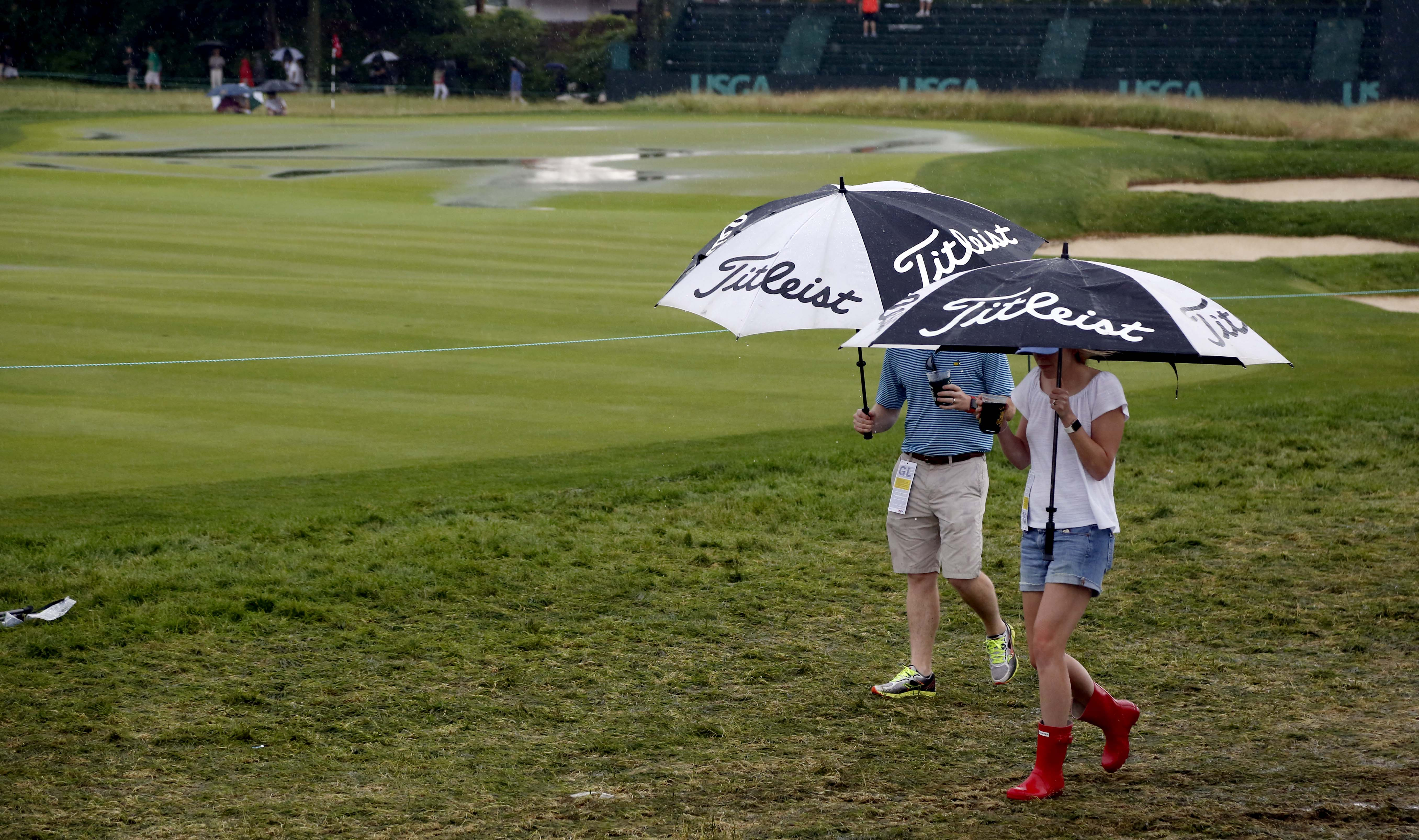 Fans leave the course during a rain delay in the first round of the U.S. Open golf championship at Oakmont Country Club on Thursday, June 16, 2016, in Oakmont, Pa. (AP Photo/Gene J. Puskar)