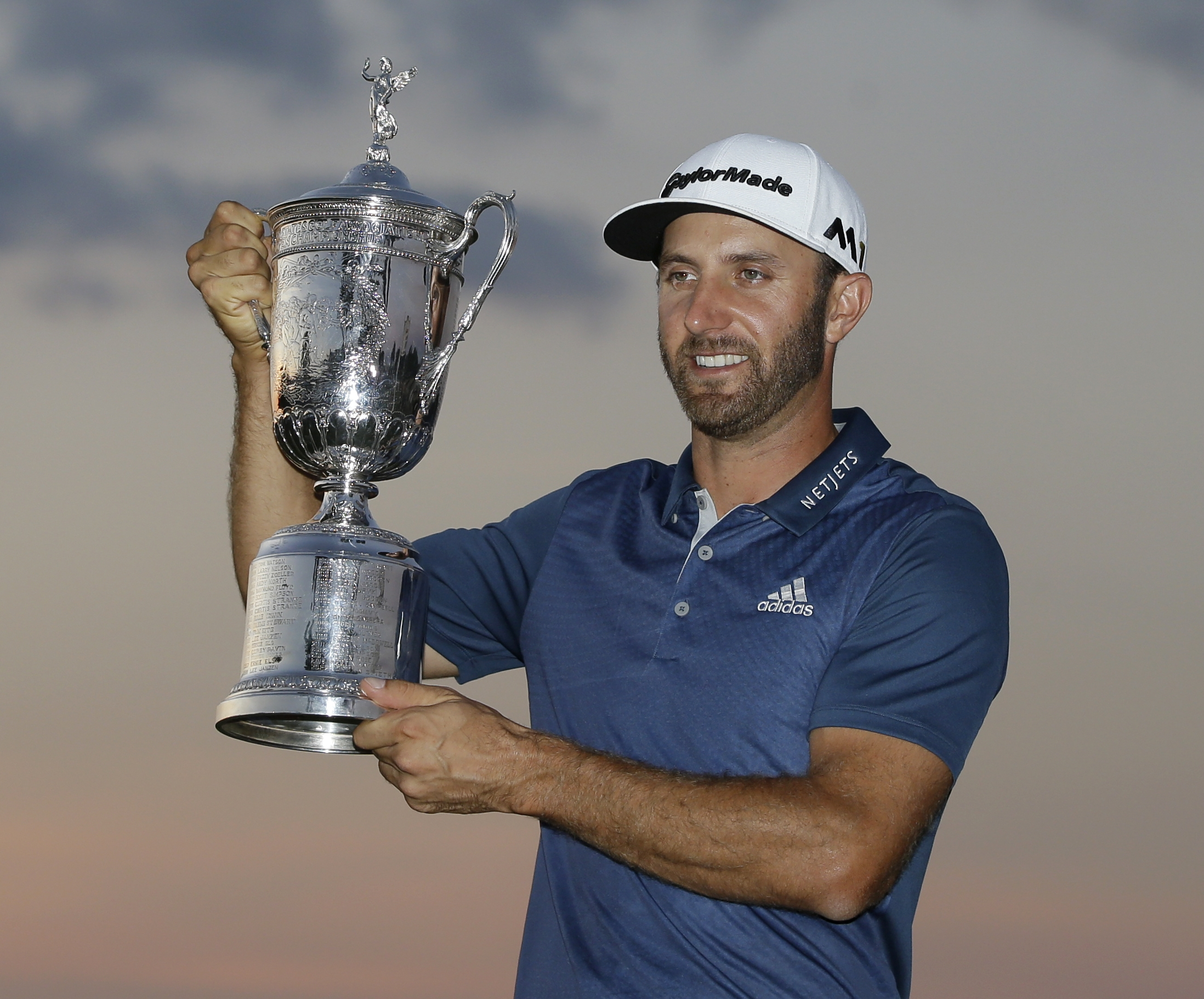 Dustin Johnson holds the trophy after winning the U.S. Open golf championship at Oakmont Country Club on Sunday, June 19, 2016, in Oakmont, Pa. (AP Photo/John Minchillo)