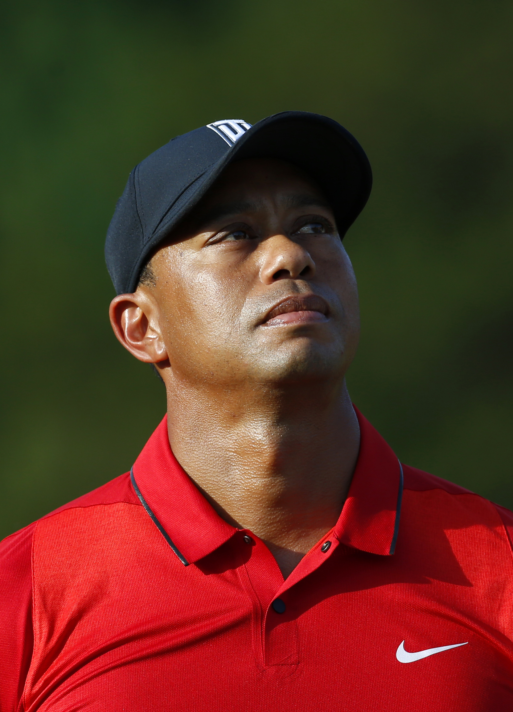 FILE - In this June 26, 2016, file photo, Tiger Woods stands on the 18th green during a trophy ceremony for Quicken Loans National PGA golf tournament winner Billy Hurley III in Bethesda, Md. Organizers say Friday, July 1, 2016, that Woods has withdrawn f