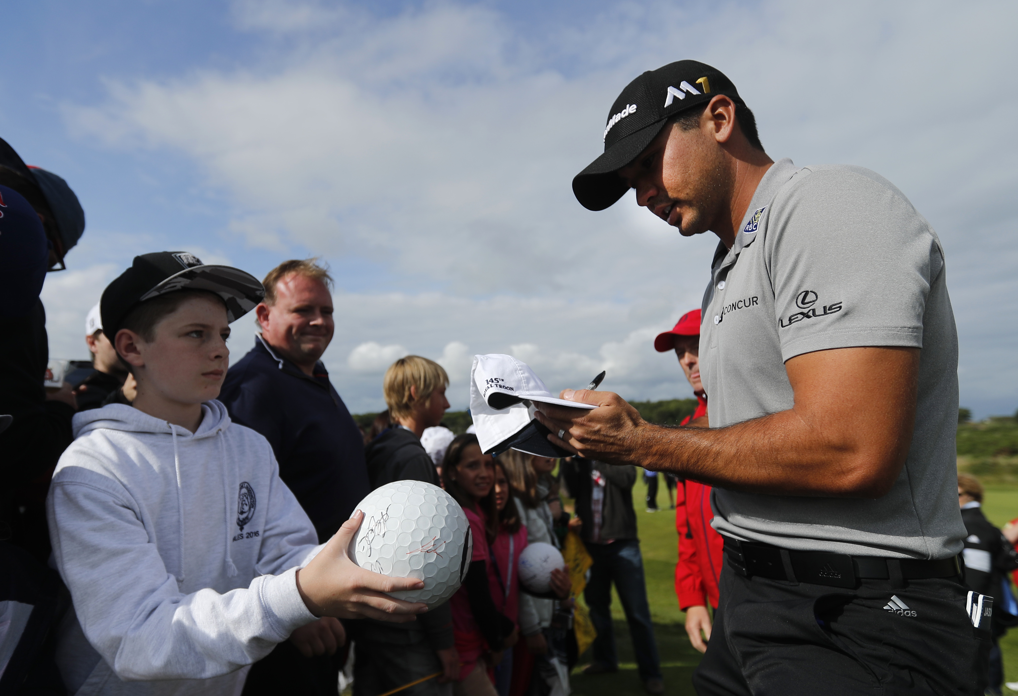 Jason Day of Australia signs autographs as he walks off the 12th green during a practice round ahead of the British Open Golf Championship at the Royal Troon Golf Club in Troon, Scotland, Tuesday, July 12, 2016. The Open starts Thursday. (AP Photo/Ben Cur