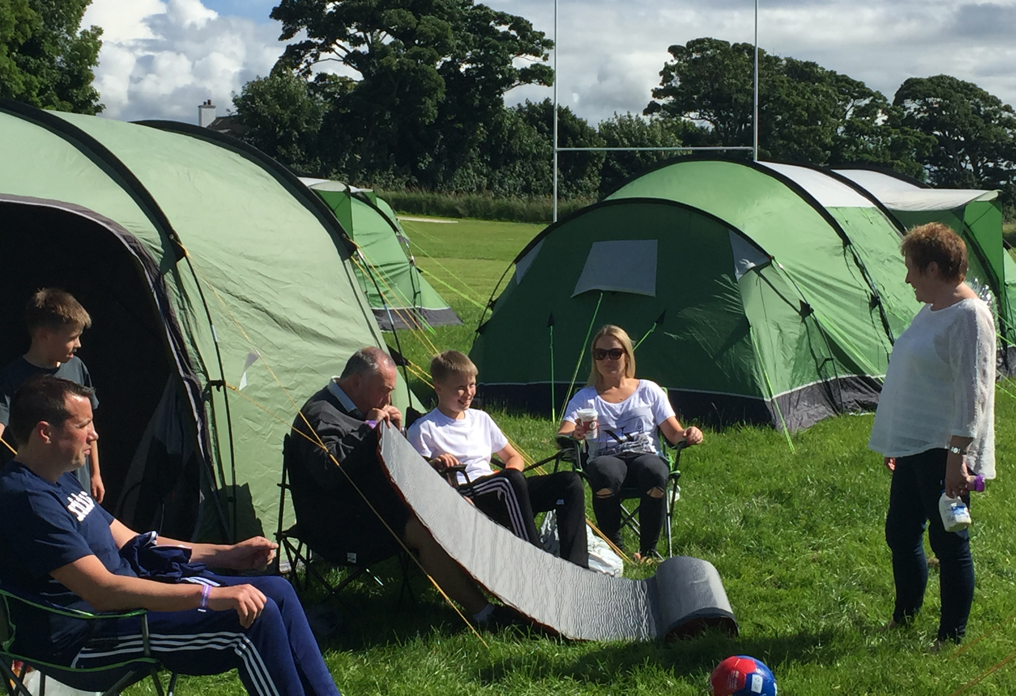 People sit outside their tent at the Marr Rugby Club in Troon, Scotland, Wednesday, July 13, 2016. For the first time, the R&A is giving a small group of fans the chance to camp out during the British Open, making things much more affordable for families