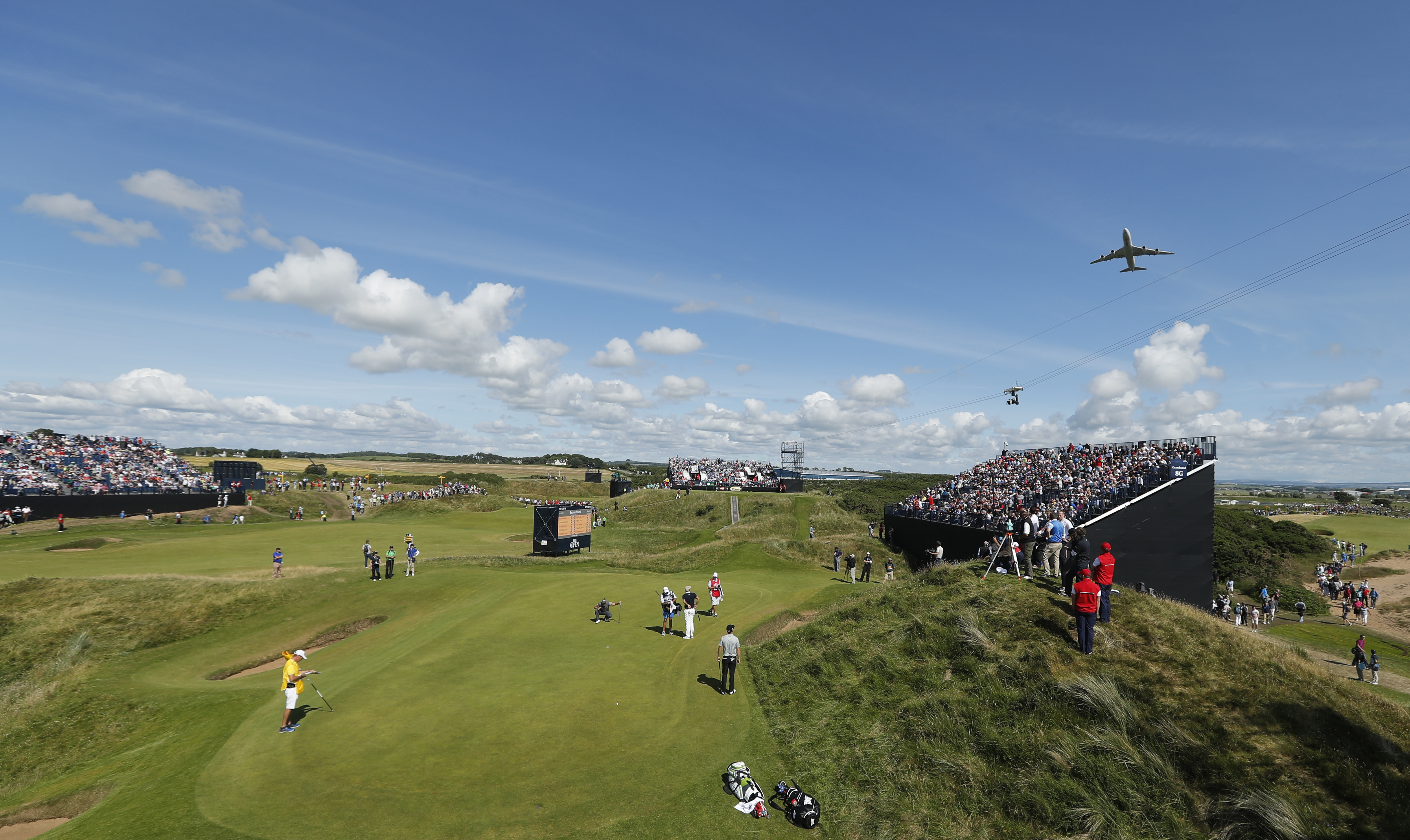 Zach Johnson of the United States, bottom right of the 8th green looks up as a cargo aircraft takes off from Preswick Airport and flies over the course during the first round of the British Open Golf Championship at the Royal Troon Golf Club in Troon, Sco