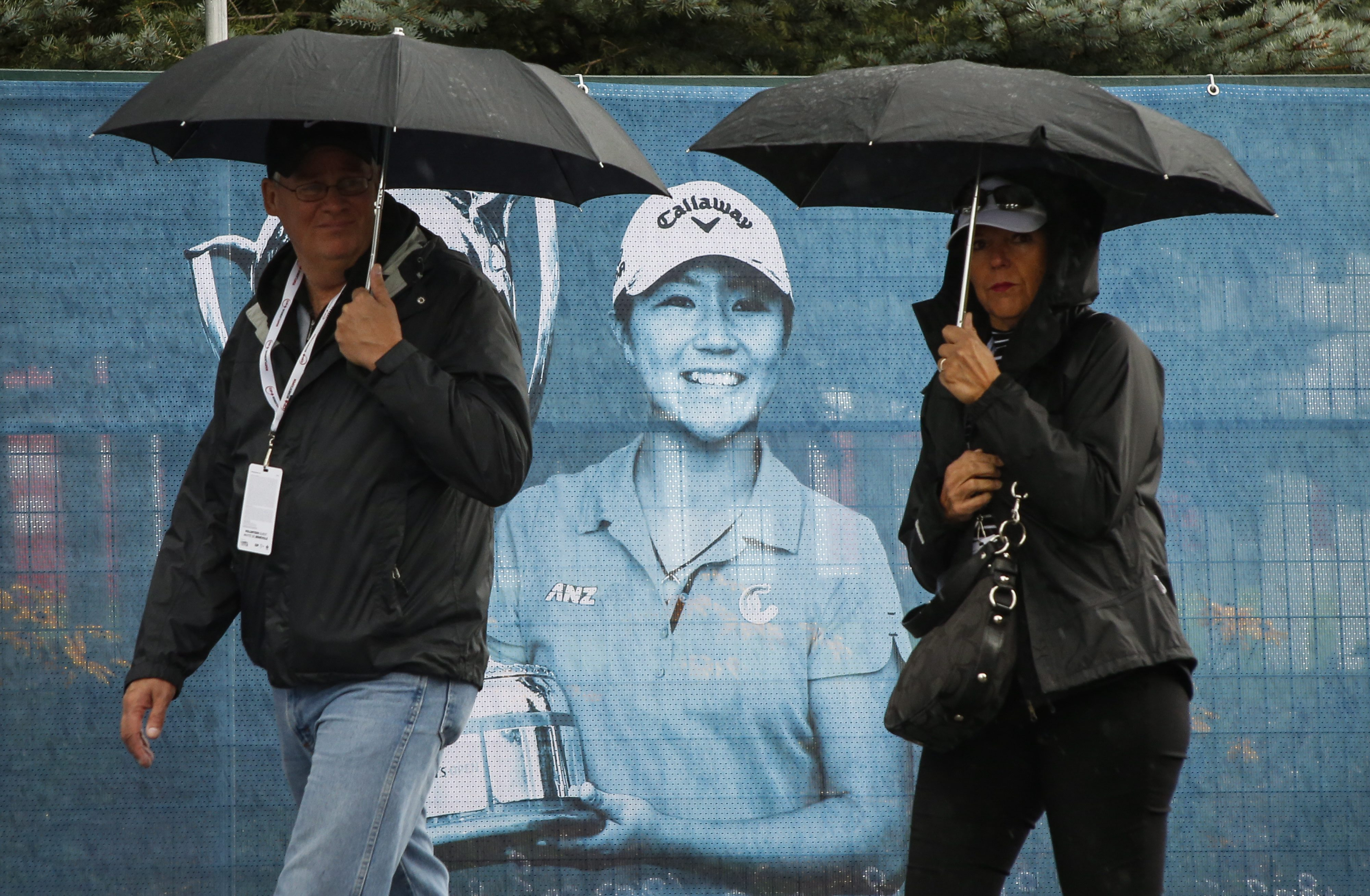 Fans walk past a banner of 2015 Canadian Open winner New Zealand's Lydia Ko during a weather delay in the first round of the Canadian Pacific Women's Open golf tournament in Priddis, Alberta, Thursday, Aug. 25, 2016. (Jeff McIntosh/The Canadian press via