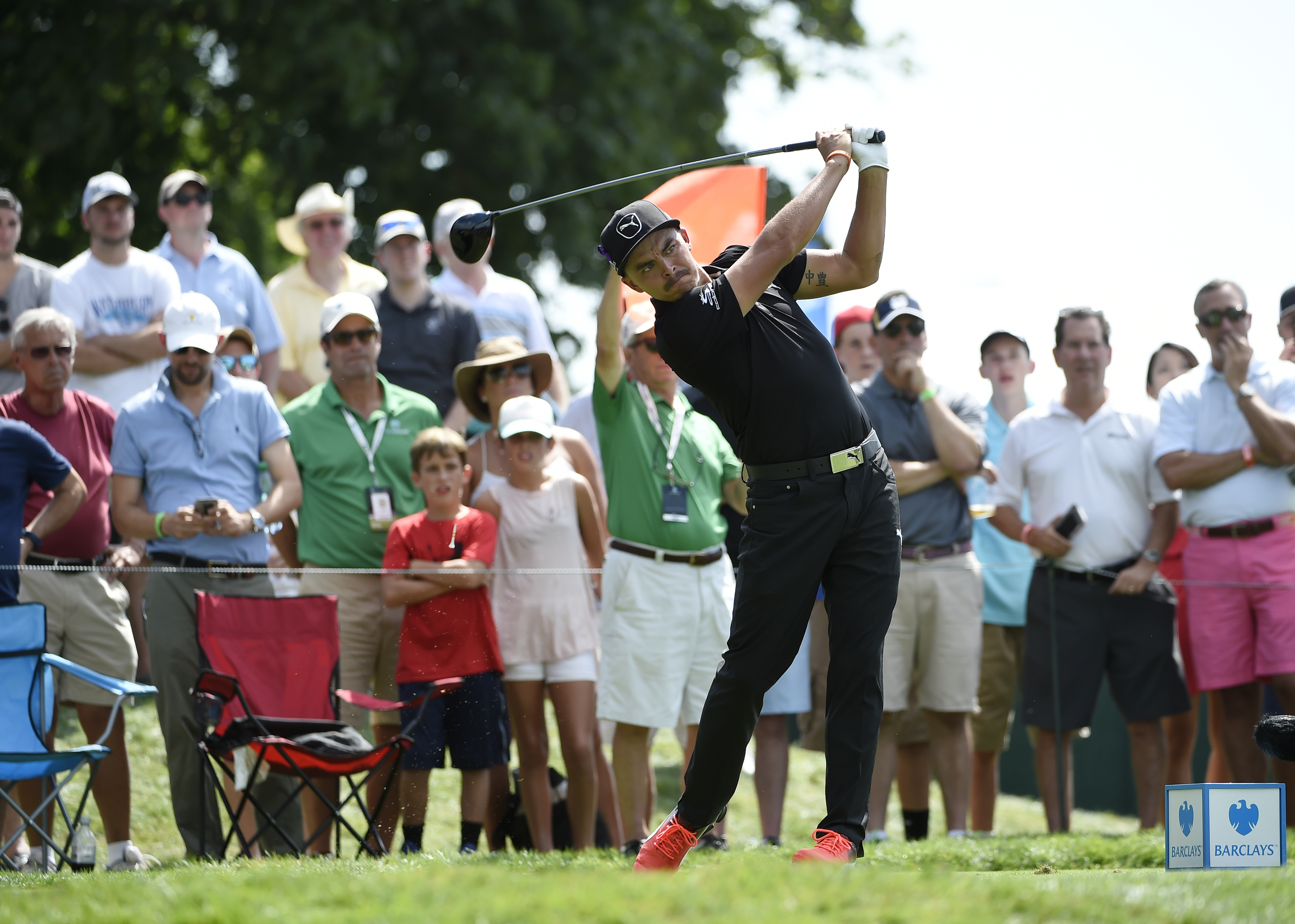 Spectators watch Rickie Fowler tee off from the 17th hole during the second round of The Barclays golf tournament in Farmingdale, N.Y., Friday, Aug. 26, 2016, (AP Photo/Kathy Kmonicek)