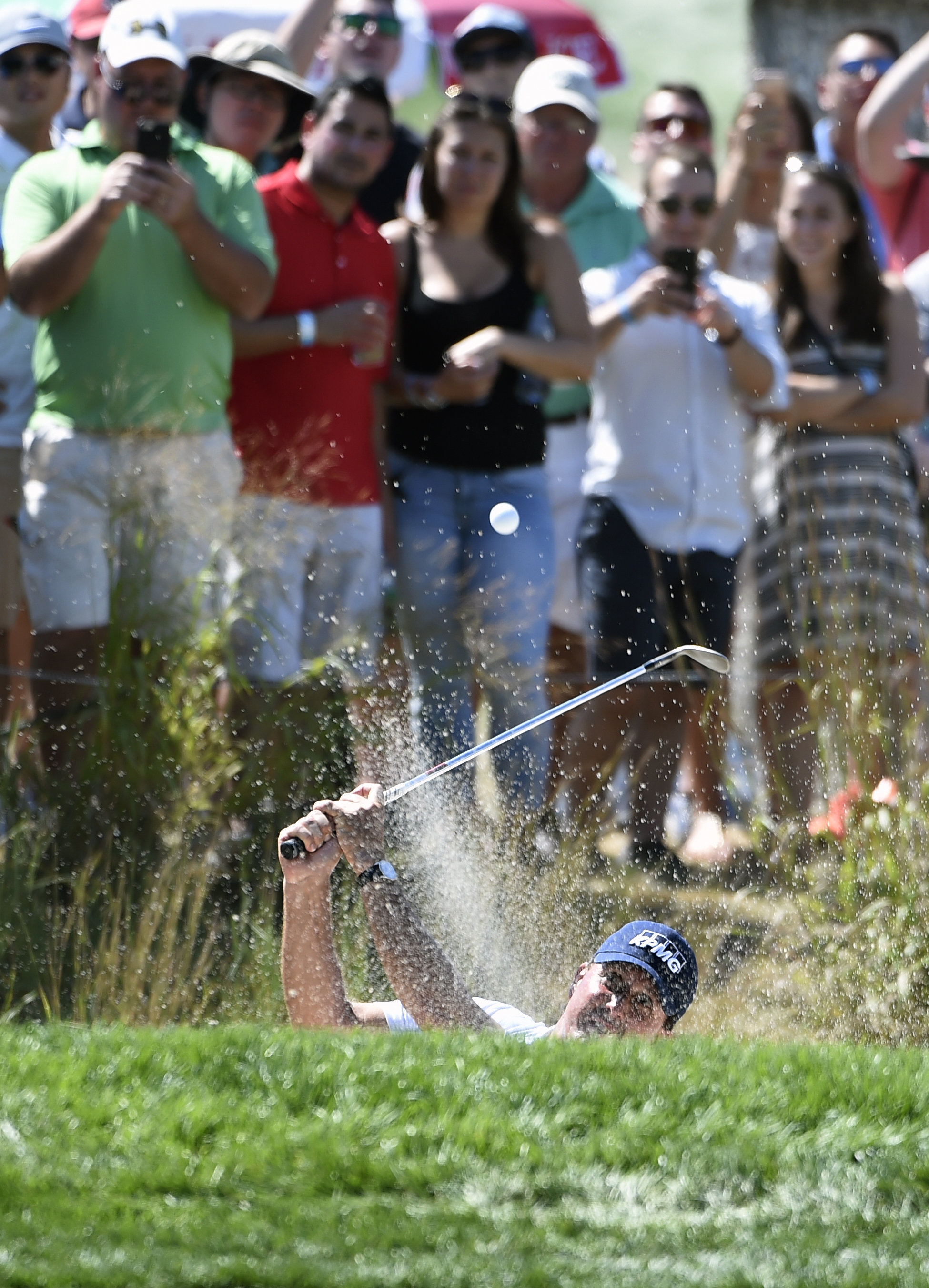 Fans watch Phil Mickelson chip out of sand trap on the 16th hole during the final round of The Barclays golf tournament in Farmingdale, N.Y., Sunday, Aug. 28, 2016. (AP Photo/Kathy Kmonicek)