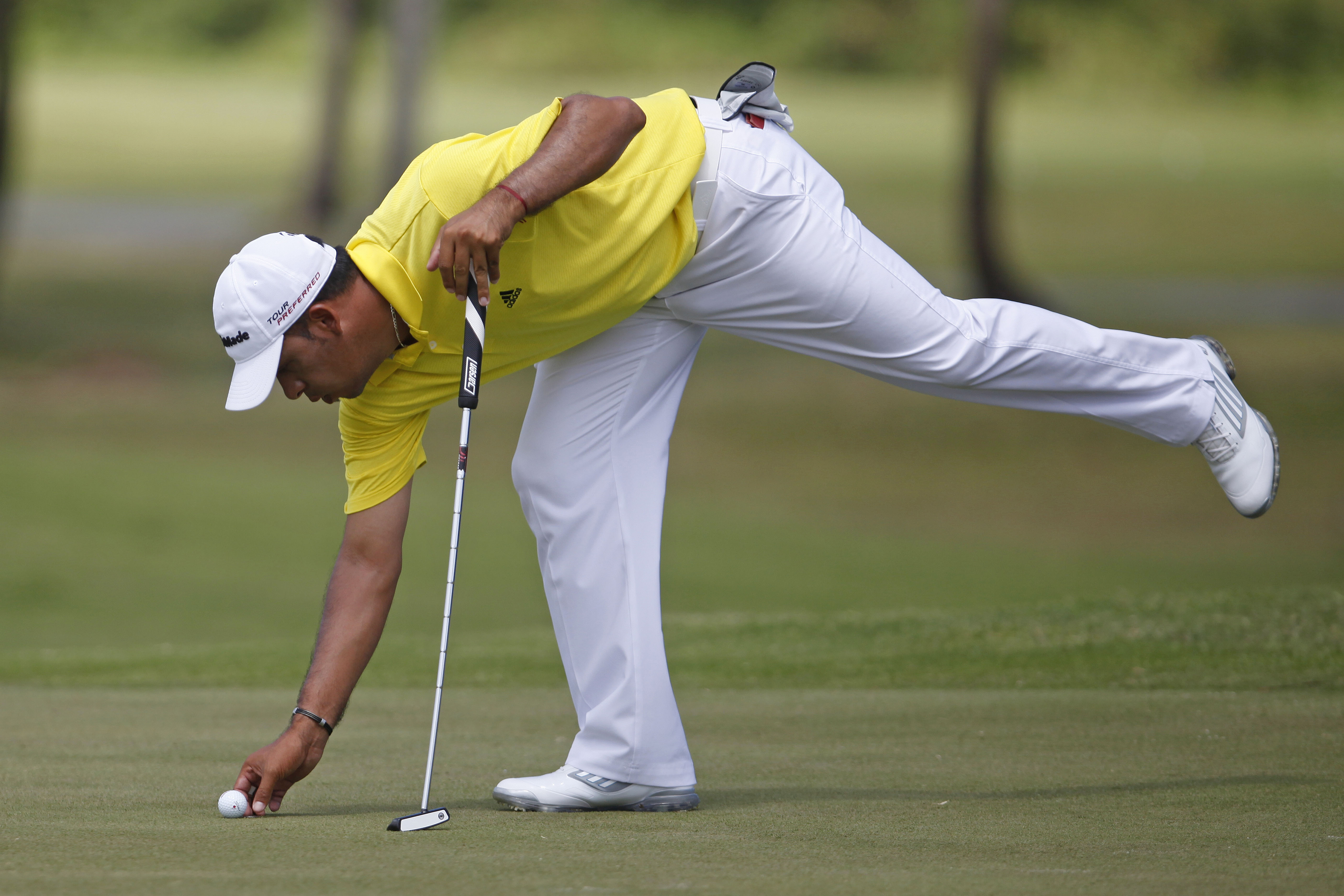 Argentinas Miguel Angel Carballo marks his ball on the putting green of the first hole during the second round of the Puerto Rico Open PGA golf tournament in Rio Grande, Puerto Rico, Friday, March 7, 2014. (AP Photo/Ricardo Arduengo)