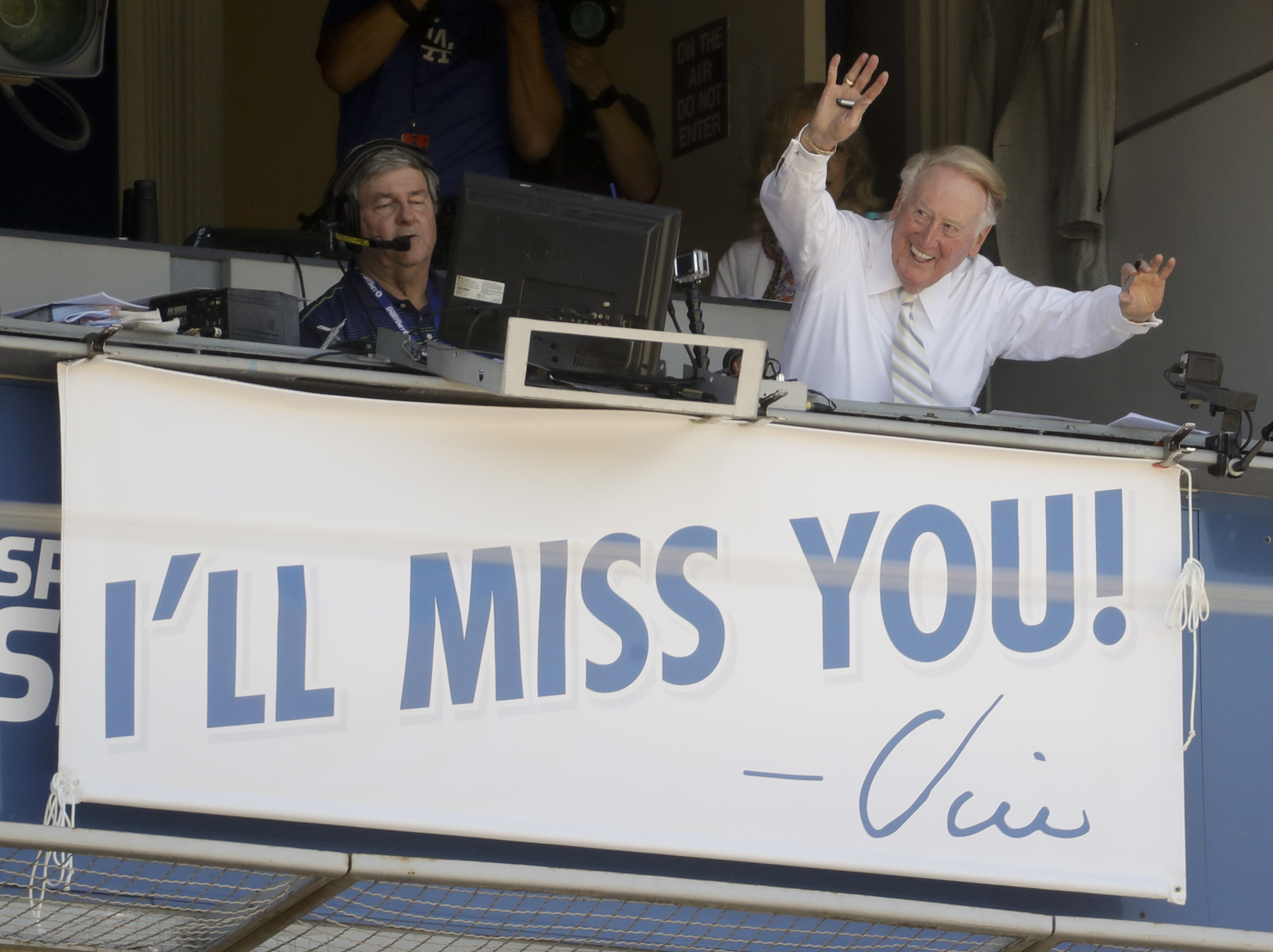 Vin Scully, a Hall of Fame broadcaster who is in the final days of his 67-year career covering Los Angeles Dodgers baseball games, waves to the fans at Dodger Stadium before a baseball game against the Colorado Rockies in Los Angeles, Sunday, Sept. 25, 20