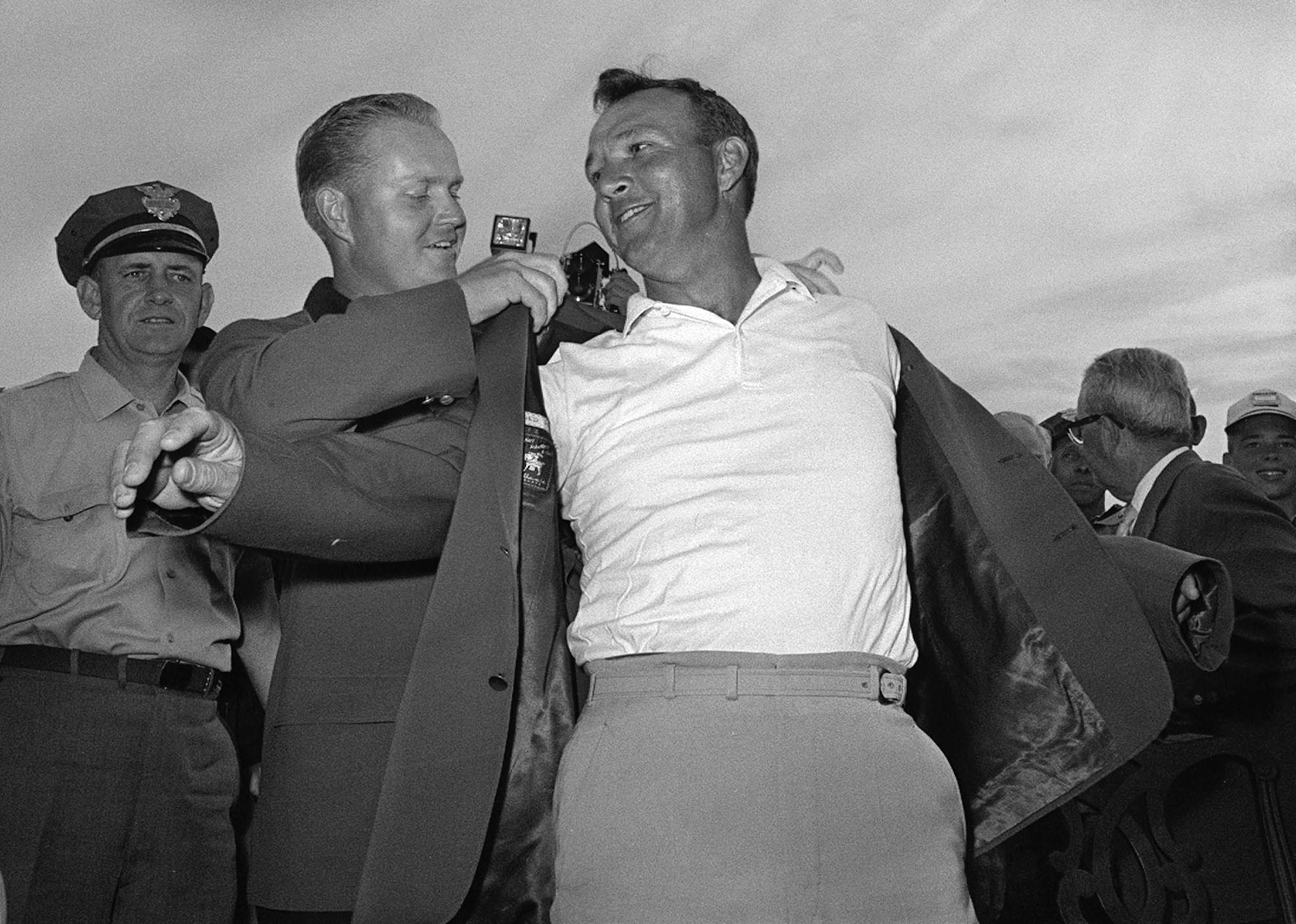 FILE - In this April 12, 1964 file photo, Arnold Palmer, right, slips into his green jacket with help from Jack Nicklaus after winning the Masters golf championship, in Augusta, Ga. Palmer, who made golf popular for the masses with his hard-charging style