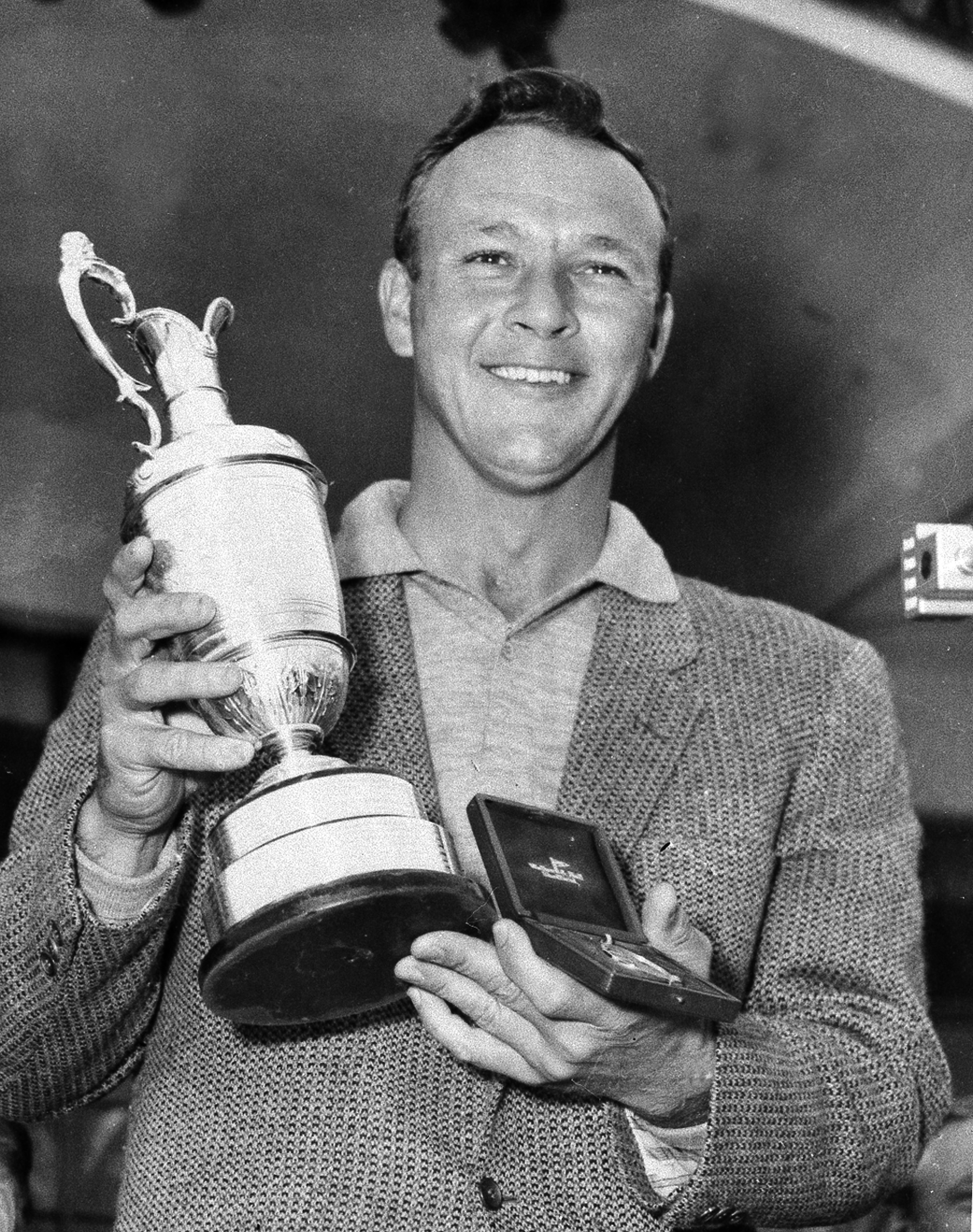File-This July 15, 1961, file photo shows Arnold Palmer smiling with his trophy and medal after winning the British Open Golf Championship by a single stroke at Royal Birkdale course in Birkdale, Lancashire, England. Palmer, who made golf popular for the