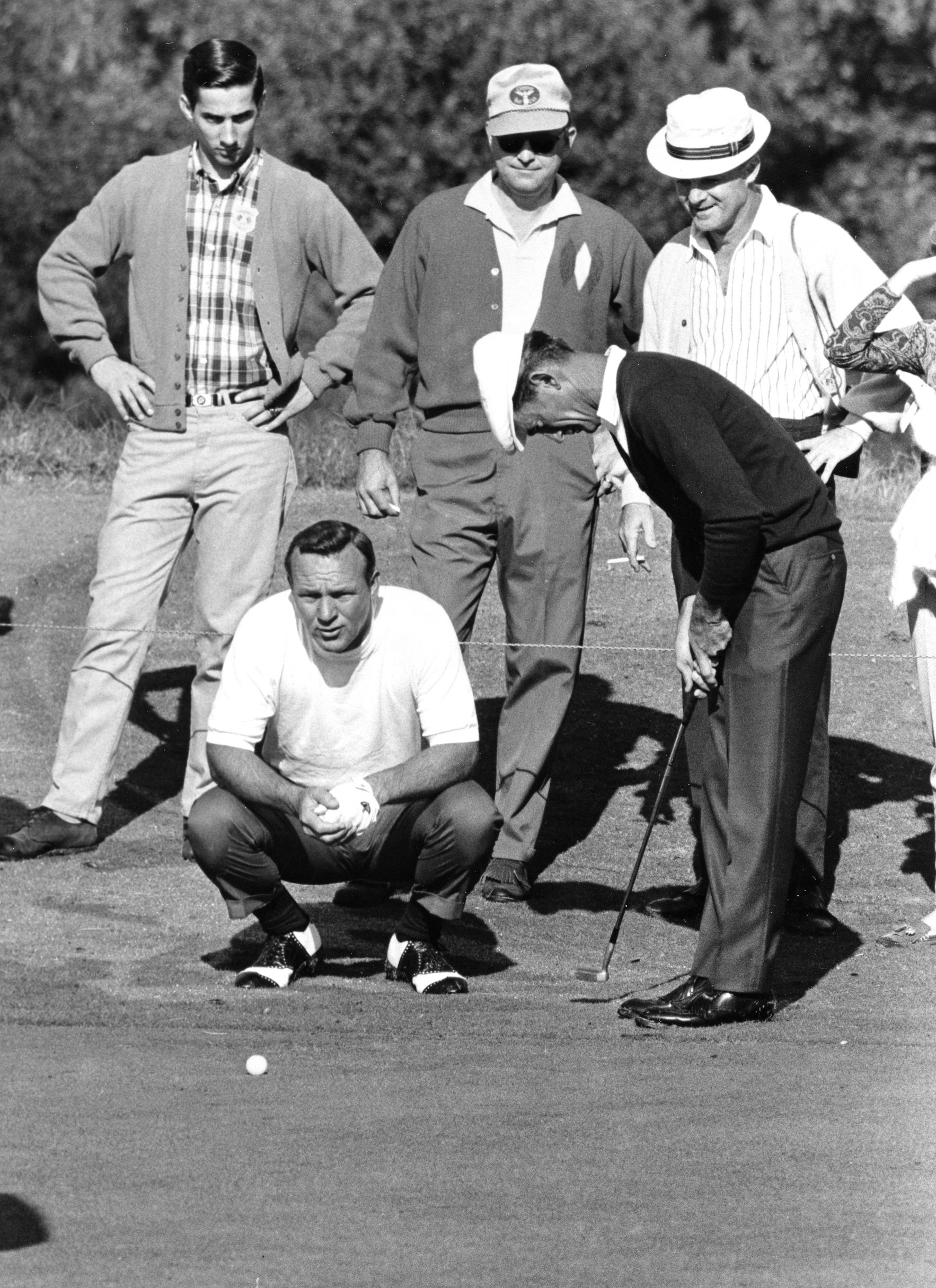FILE - In this October 1967 file photo, Arnold Palmer, kneeling, eyes a putt for U.S. Ryder Cup teammate Gardner Dickinson during the second round against the British team in Houston. Dickinson won an NCAA title at Louisiana State and seven times on the P