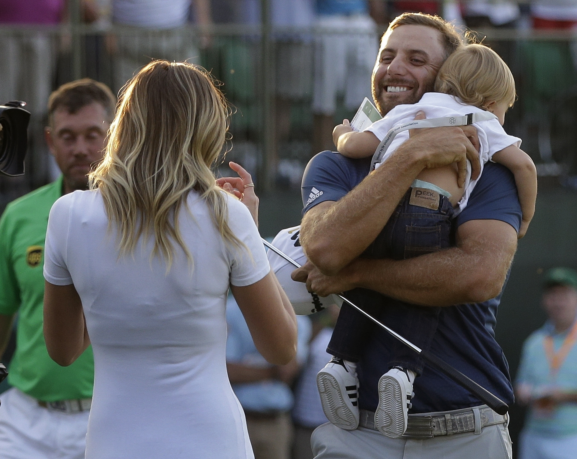 FILE - In this June 19, 2016, file photo, Dustin Johnson, right, greets his fiance, Paulina Gretzky, as he holds their son, Tatum Gretzky, on the 18th hole during the final round of the U.S. Open golf championship,  at Oakmont Country Club, in Oakmont, Pa