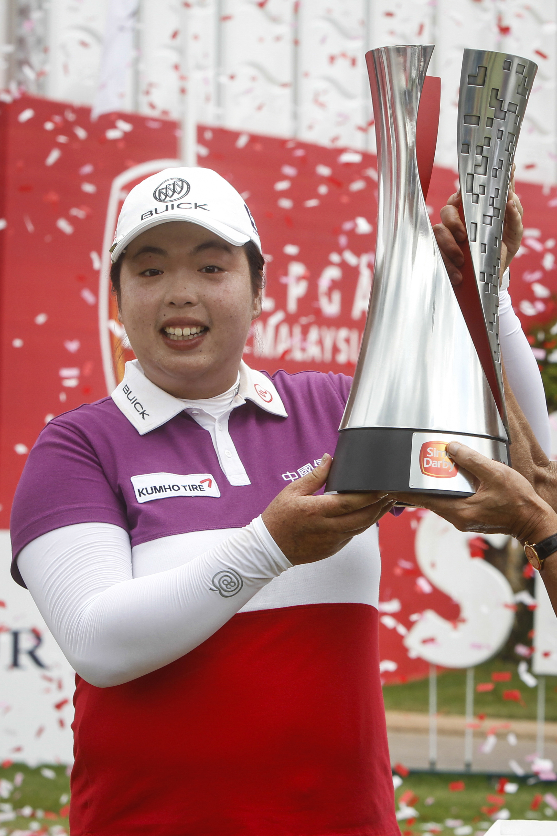 Shanshan Feng of China holds up her trophy after winning the LPGA golf tournament at Tournament Players Club (TPC) in Kuala Lumpur, Malaysia, Sunday, Oct. 30, 2016. (AP Photo/Joshua Paul)