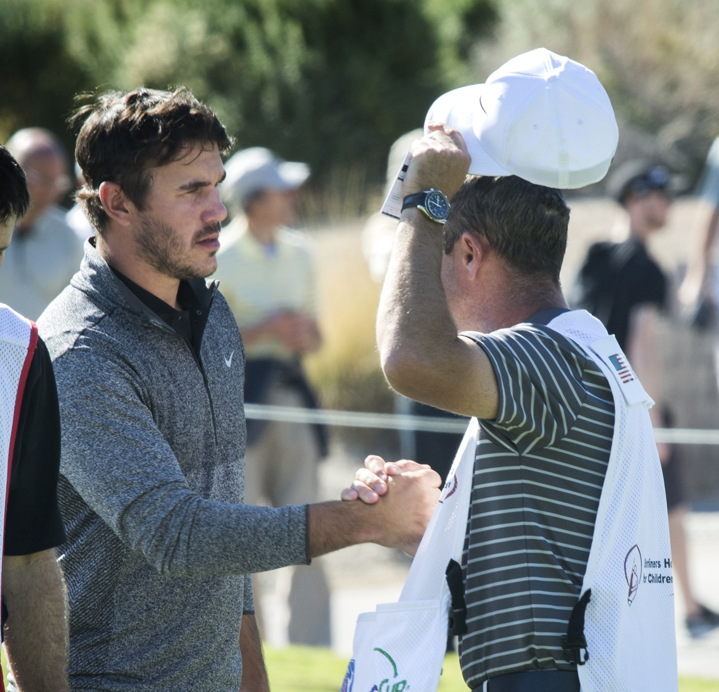 Brooks Koepka, left, shakes hands with a caddie on the ninth hole Thursday, Nov. 3, 2016, on the opening day of the Shriners Hospitals for Children Open golf tournament in Las Vegas. (Jeff Scheid/Las Vegas Review-Journal via AP)