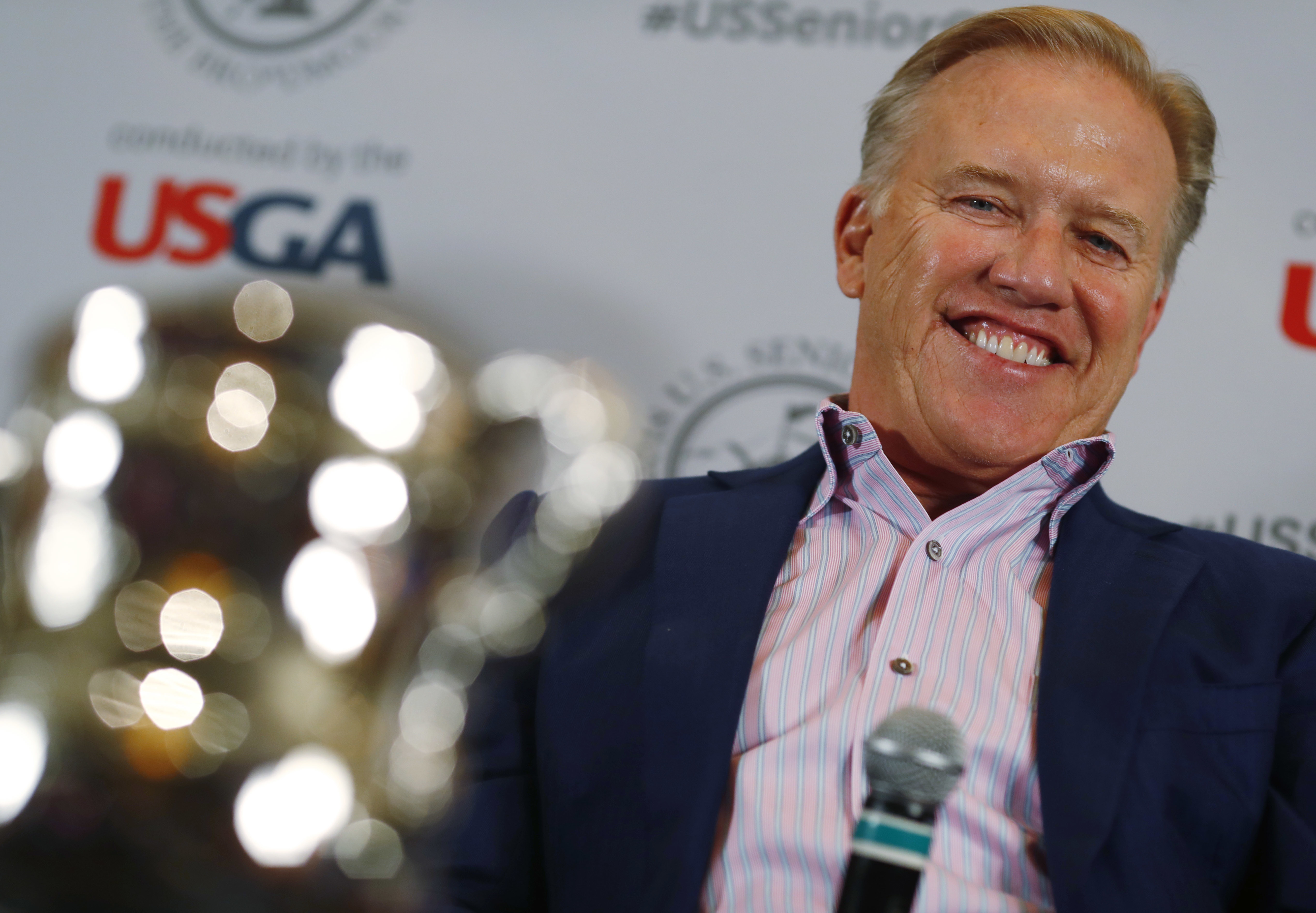 Denver Broncos general manager John Elway jokes with reporters after he was introduced as the honorary chairman of the 39th U.S. Senior Open, which will be held at the Broadmoor Golf Club in Colorado Springs, Colo., during a news conference at one of the