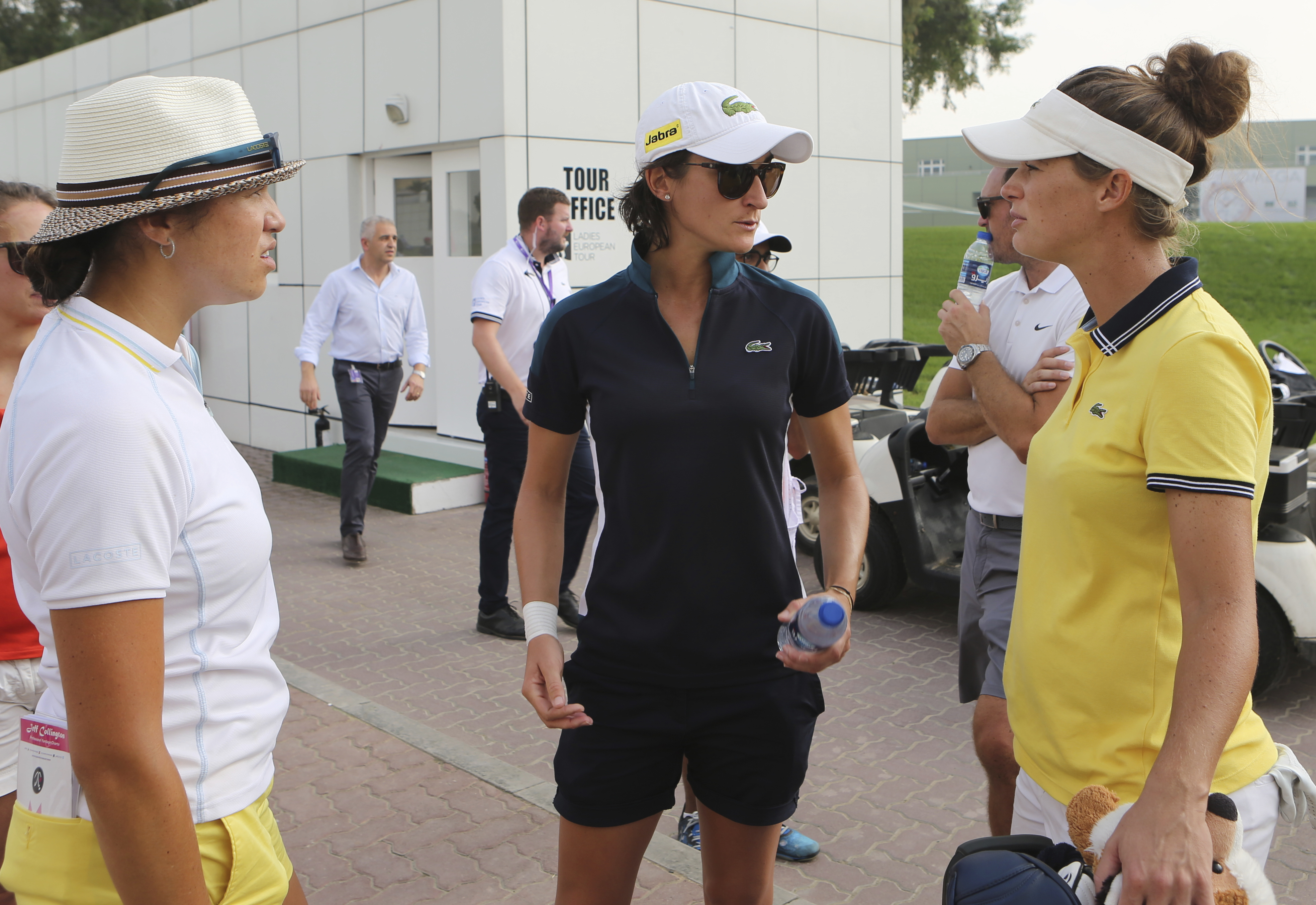 Anne-Lise Caudal of France, middle, talks to her fellow country players after her caddie collapsed on the course, which led to an immediate suspension of play during the 1st round of Dubai Ladies Masters golf tournament in Dubai, United Arab Emirates, Wed