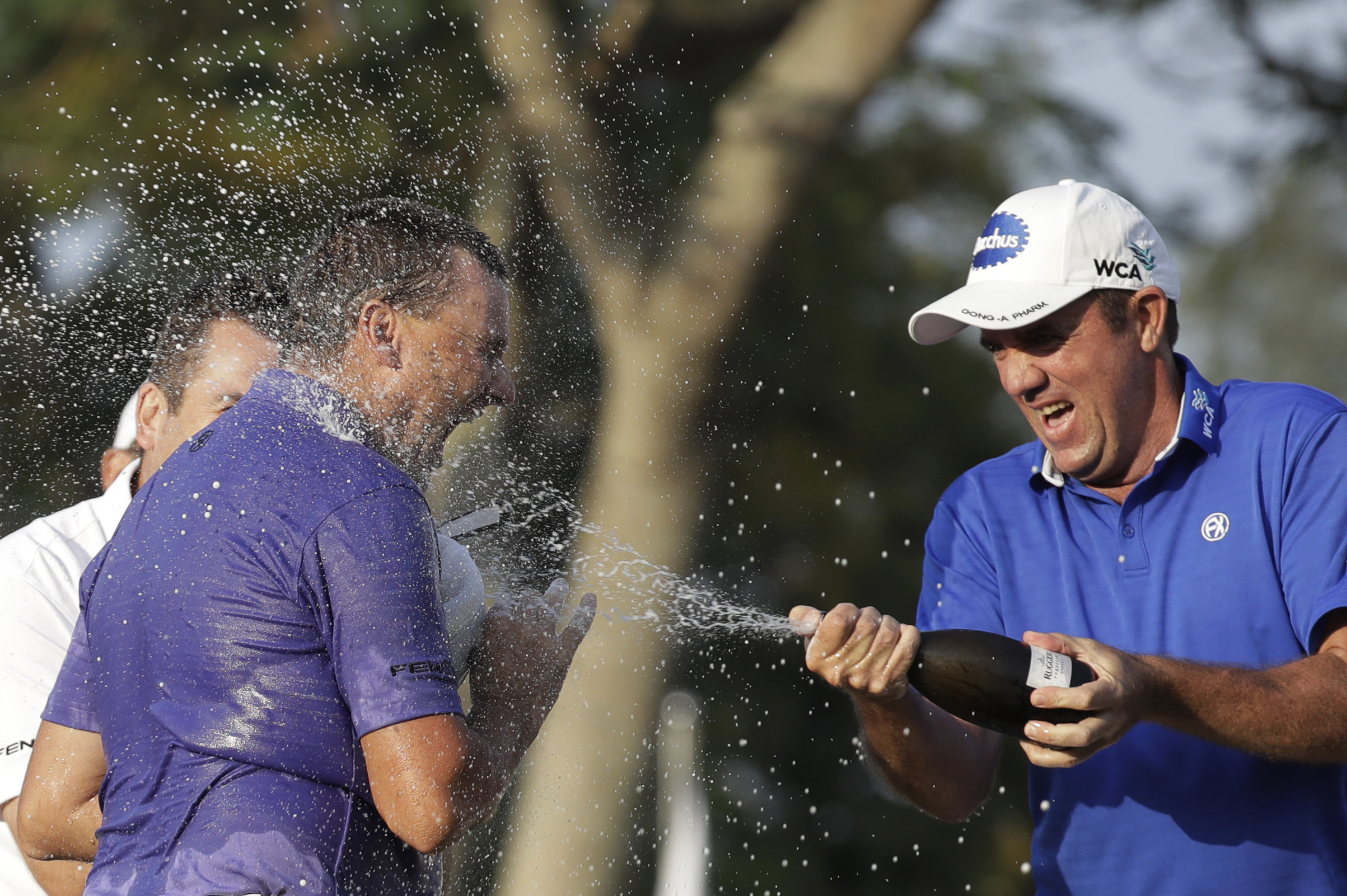 Australia's Sam Brazel, left, celebrates with his supporter after winning the Hong Kong Open golf tournament in Hong Kong, Sunday, Dec. 11, 2016. Brazel birdied the 18th hole to narrowly edge Rafa Cabrera Bello of Spain to capture the Hong Kong Open on Su