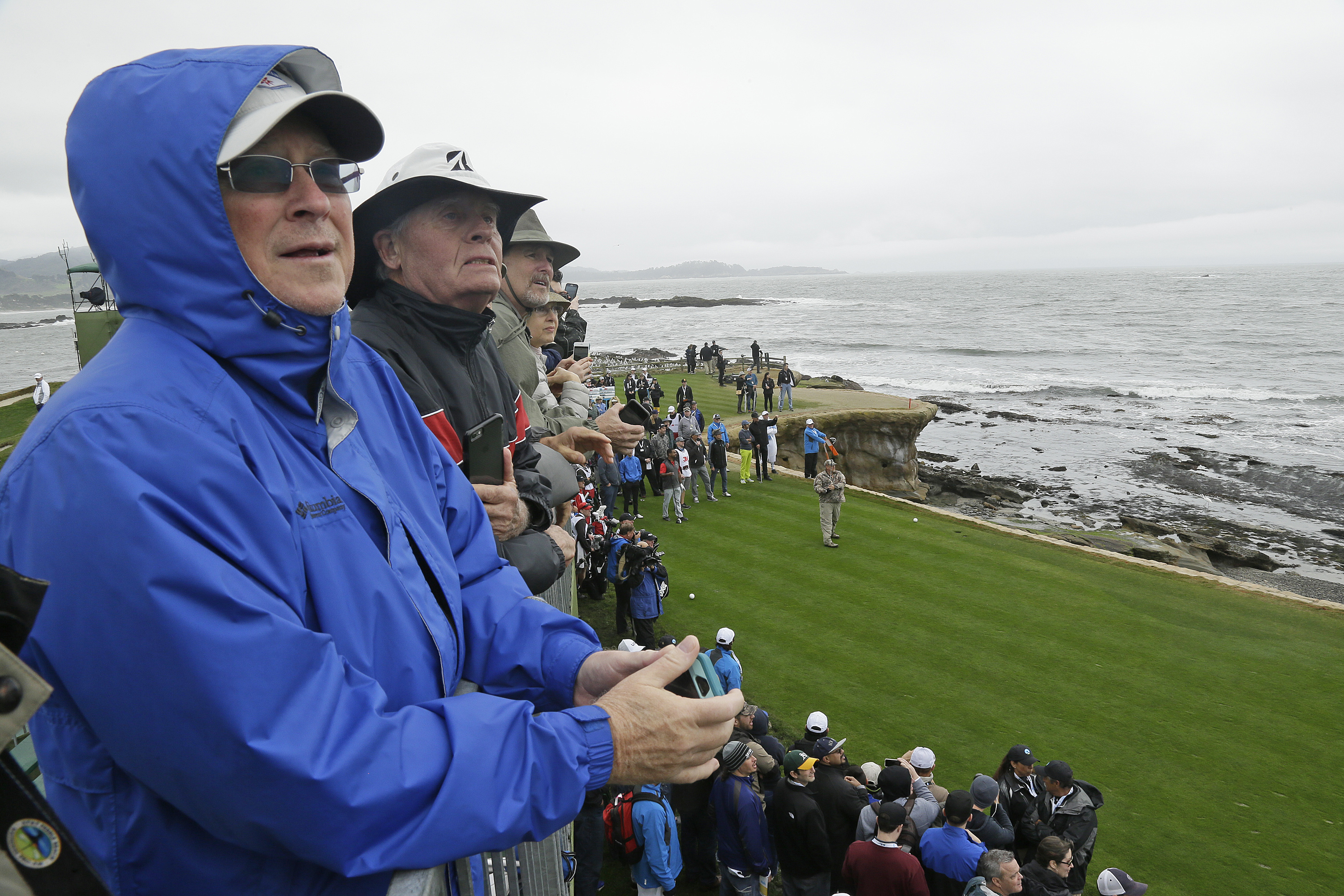 Spectators watch Daniel Lawrence Whitney, better known as, Larry the Cable Guy, hit from the 18th tee during the celebrity challenge event of the AT&T Pebble Beach National Pro-Am golf tournament Wednesday, Feb. 8, 2017, in Pebble Beach, Calif. (AP Photo/