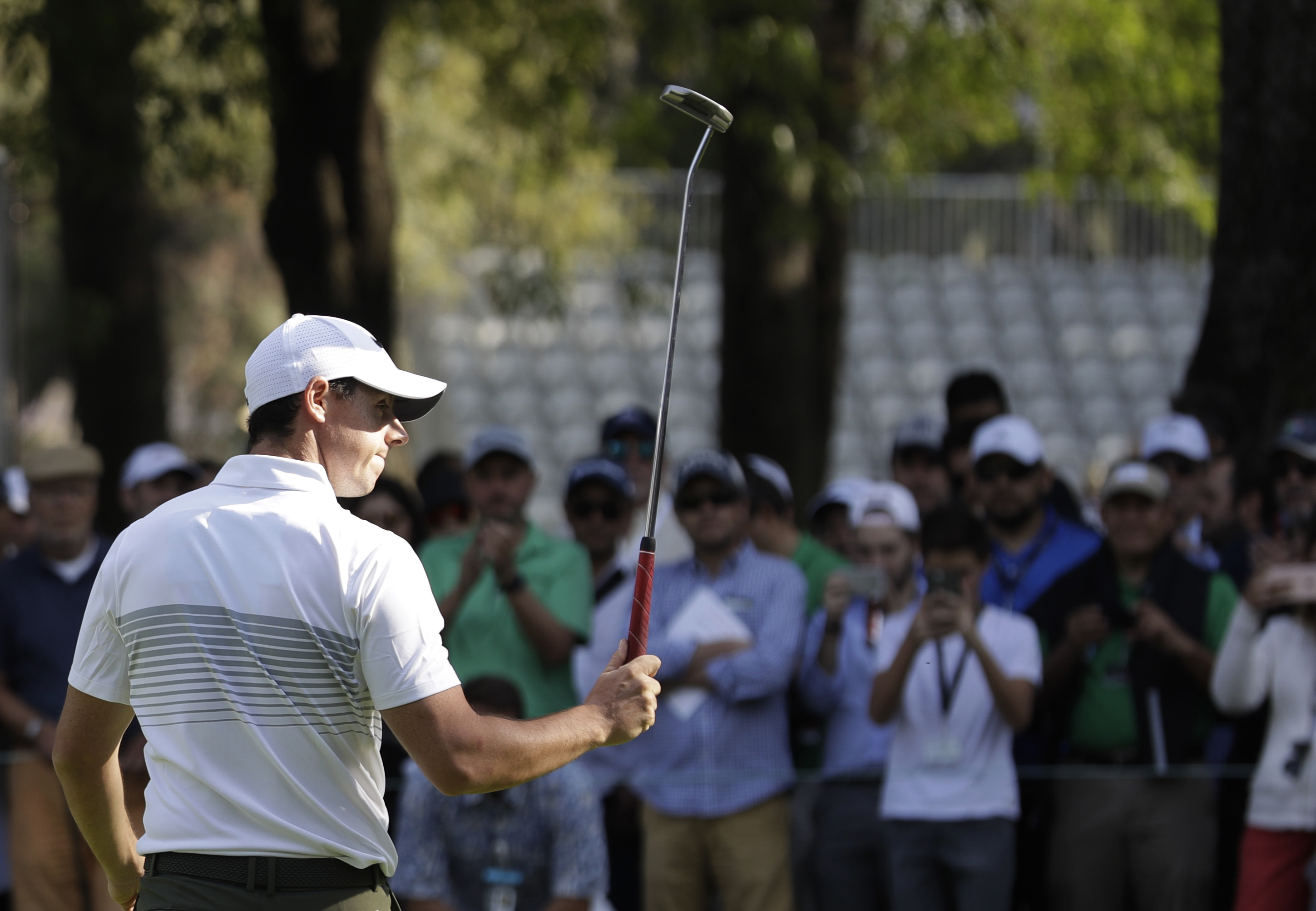Rory McIlroy of Northern Ireland gestures to fans with his club as he leaves the 9th hole after finishing round one of the Mexico Championship at Chapultepec Golf Club in Mexico City, Thursday, March 2, 2017. All but one of the world's top 50 golfers are