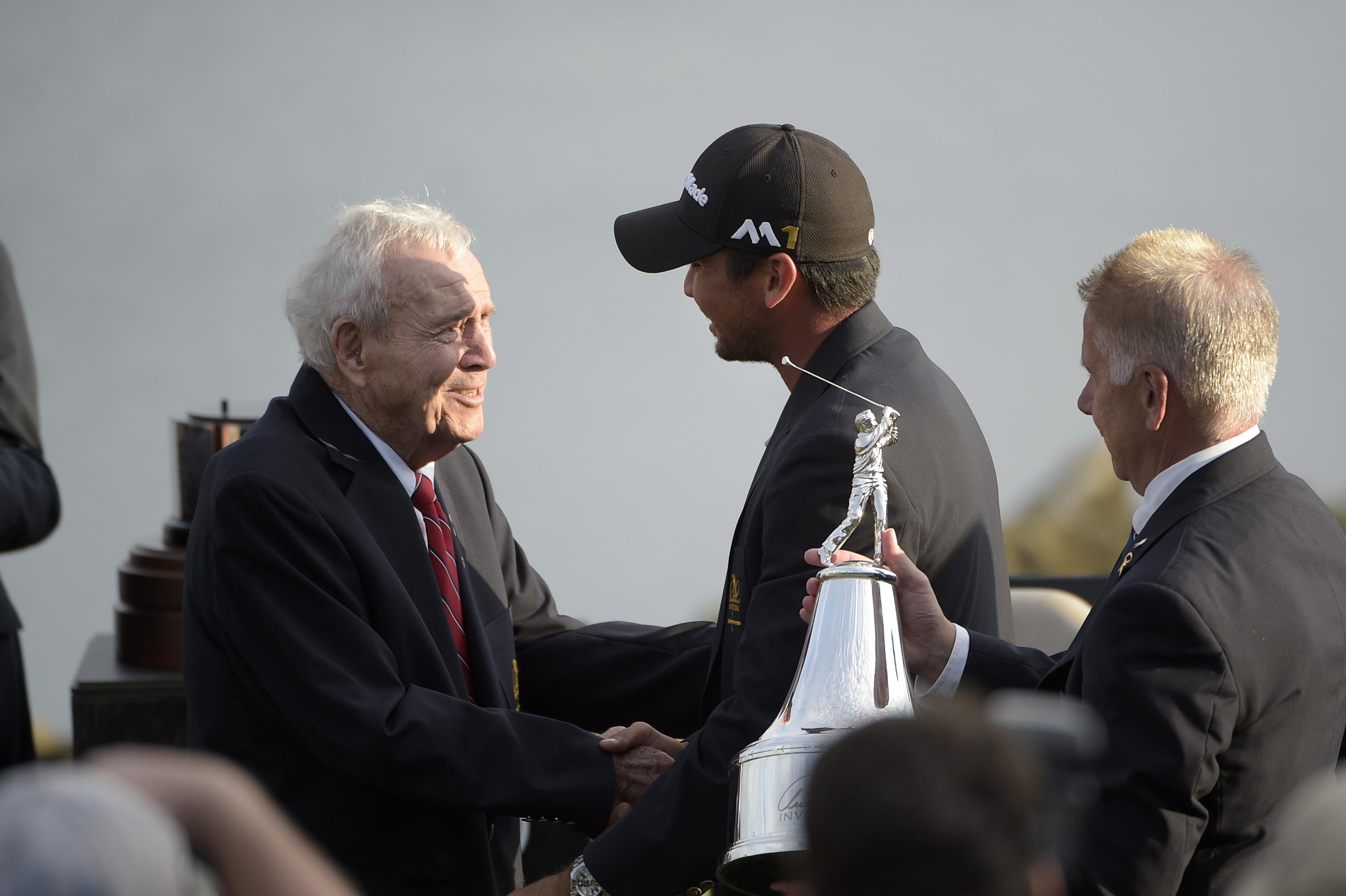 FILE - In this March 20, 2016, file photo, Arnold Palmer, left, congratulates Jason Day, center, of Australia, after Day won the Arnold Palmer Invitational golf tournament in Orlando, Fla. (AP Photo/Phelan M. Ebenhack, File)