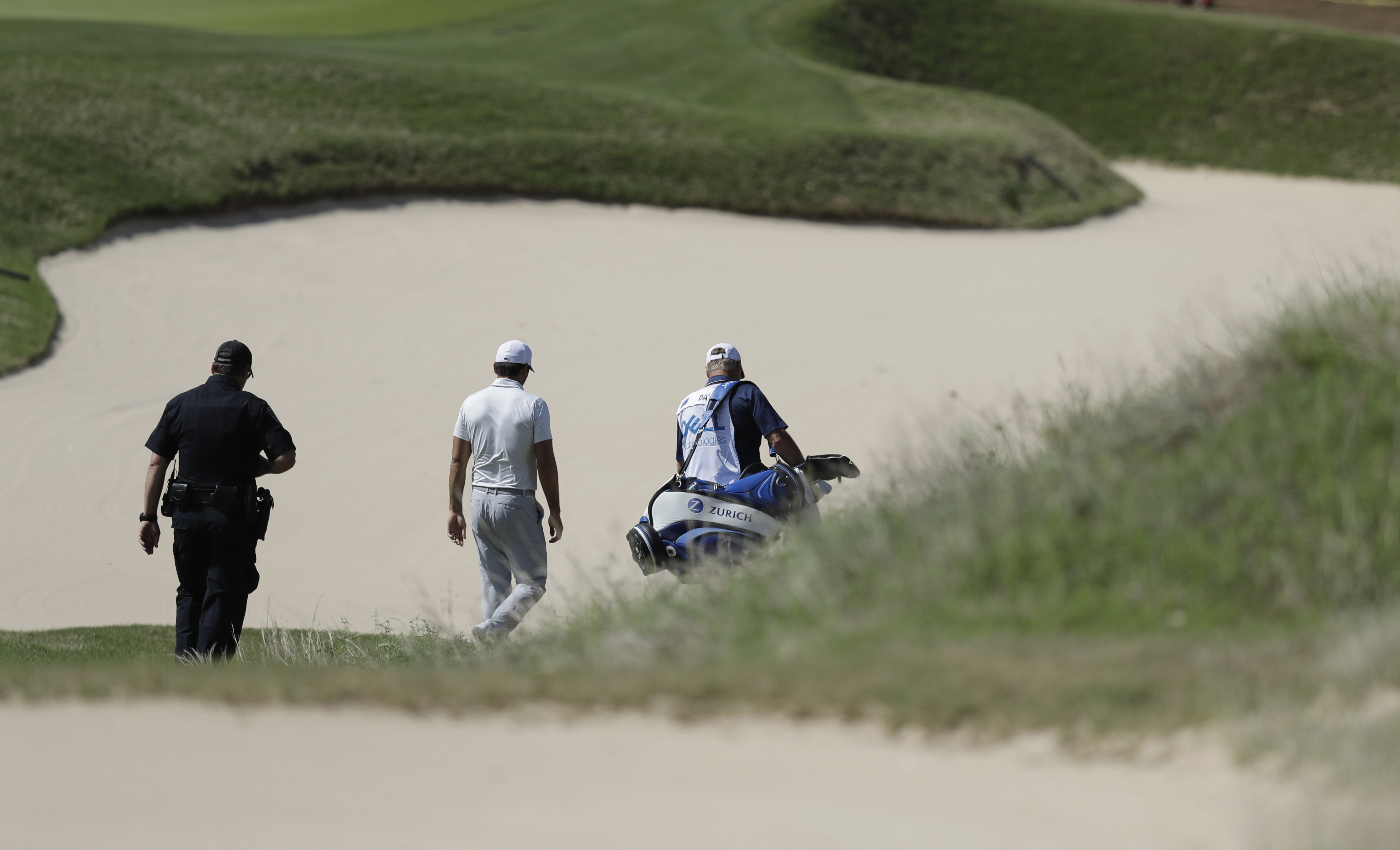 Defending champion Jason Day, center, of Australia, center, down the seventh hole after he conceded to Pat Perez after six holes of play during round-robin play at the Dell Technologies Match Play golf tournament at Austin County Club, Wednesday, March 22
