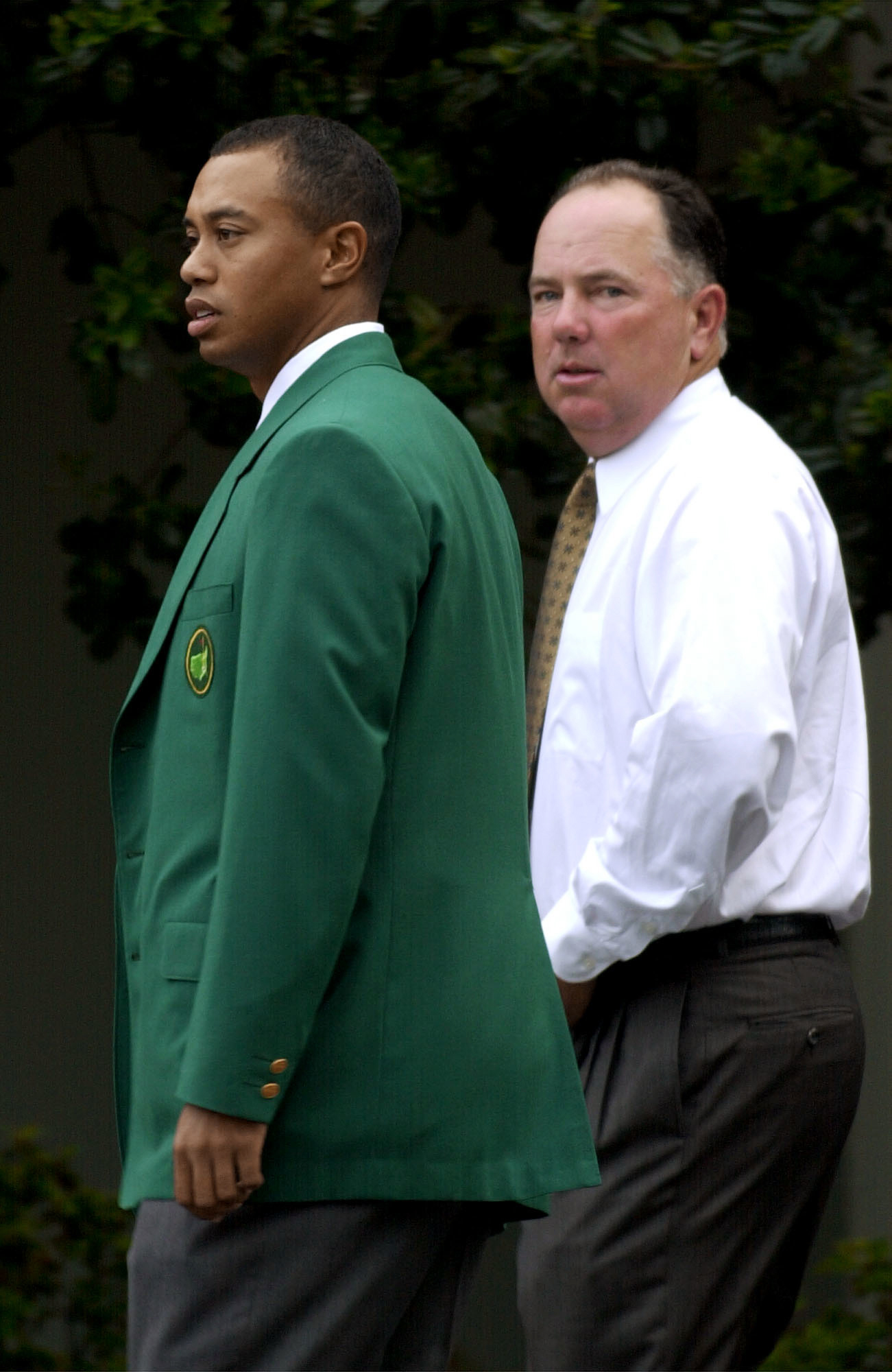 FILE - In this Tuesday, April 9, 2002, file photo, Defending Masters Champion Tiger Woods, left, and 1998 Masters Champion Mark O'Meara, right, arrive at the Augusta National Golf Club for the annual Champions dinner at the 2002 Masters, in Augusta, Ga. O