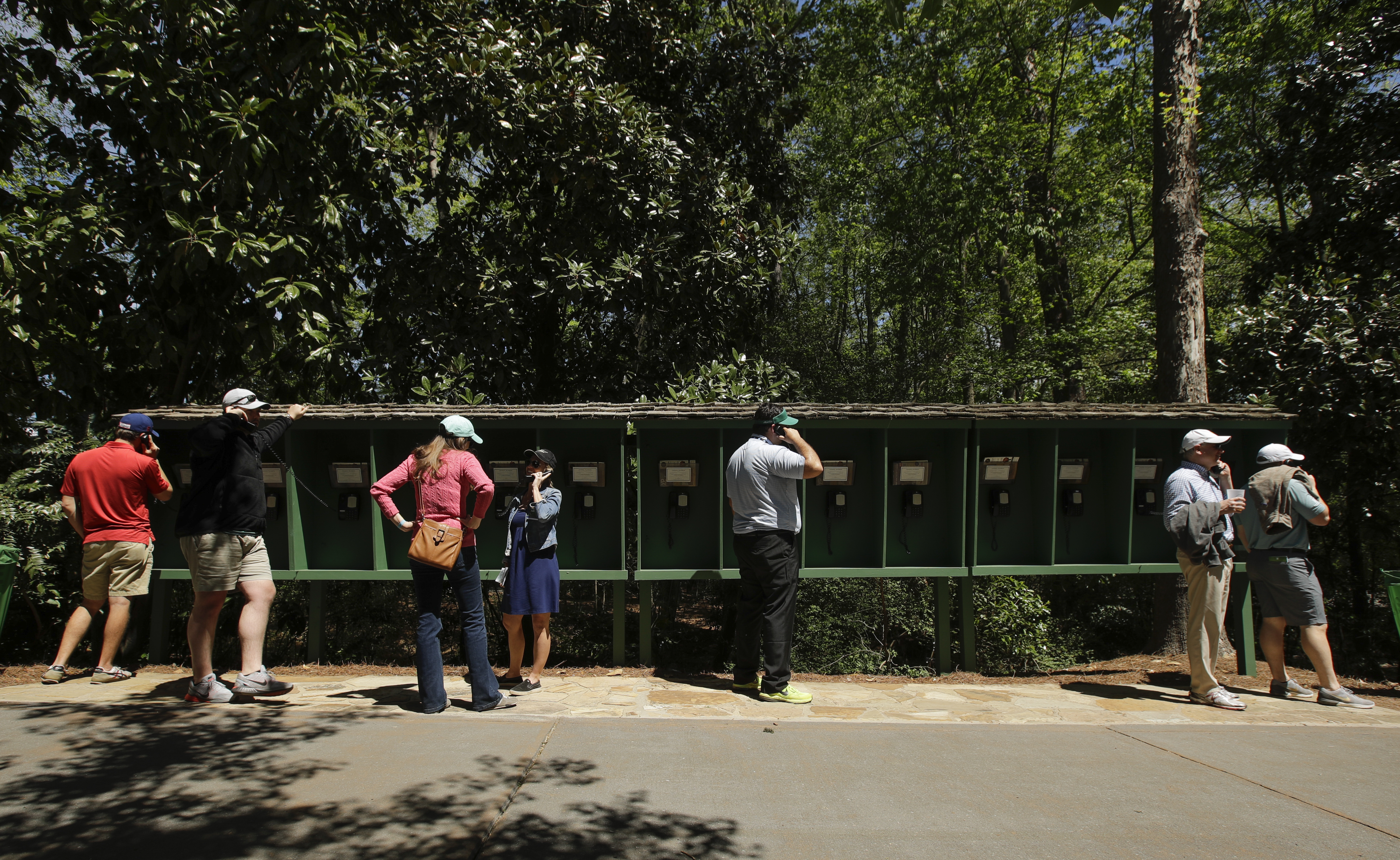Patrons use pay phones on the Augusta National golf course during the third round of the Masters golf tournament Saturday, April 8, 2017, in Augusta, Ga. No cell phones are allowed on the course. (AP Photo/Charlie Riedel)