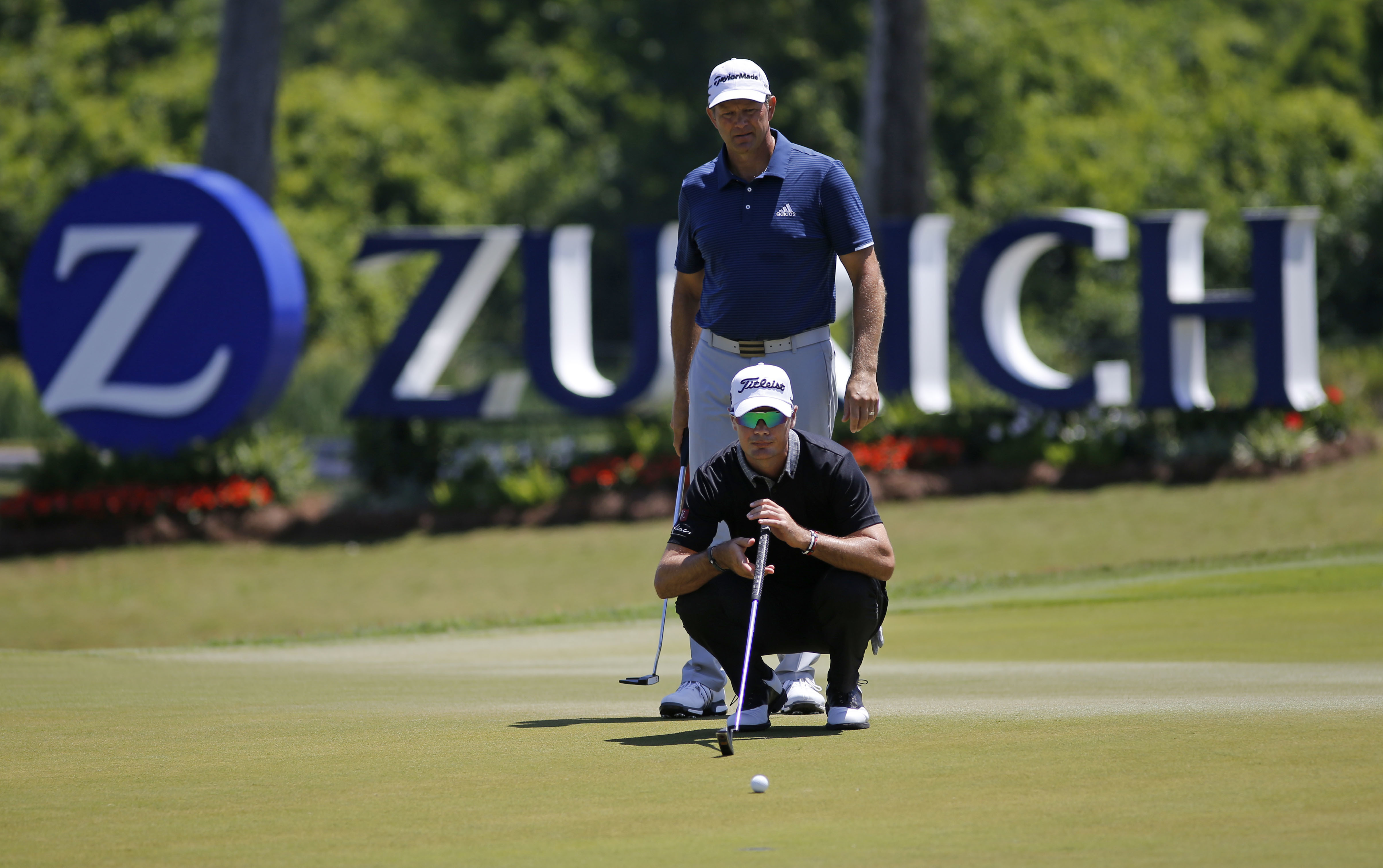 South Africa's Retief Goosen, standing, watches as teammate and compatriot Tyrone Van Aswegen lines up a shot on the 17th green, during the first round of the PGA Zurich Classic golf tournament's new two-man team format at TPC Louisiana in Avondale, La.,