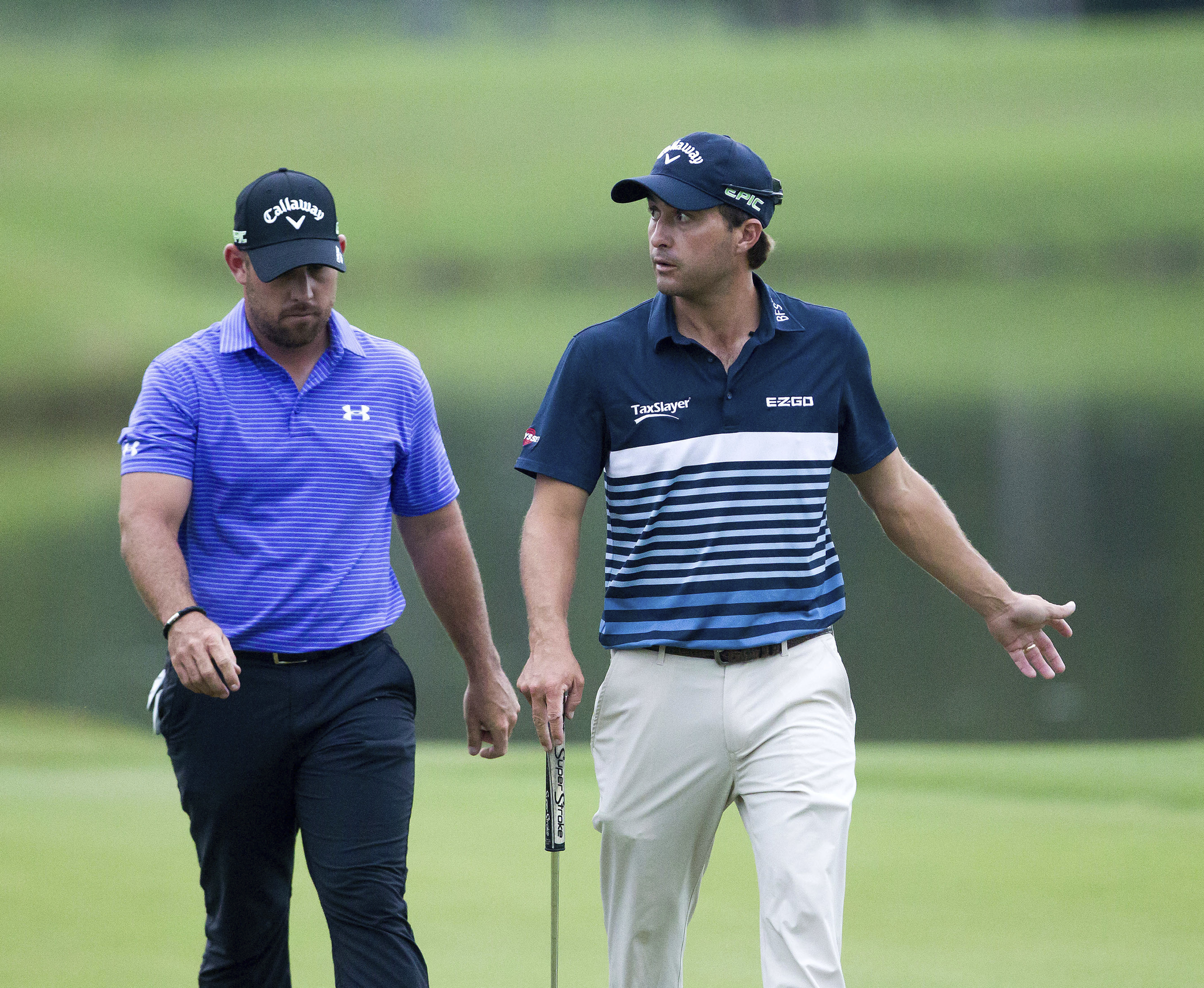 Teammates Scott Brown, left, and Kevin Kisner leave the 17th green with par during the final round of the PGA Zurich Classic golf tournament's new two-man team format at TPC Louisiana in Avondale, La., Sunday, April 30, 2017. (AP Photo/Scott Threlkeld)