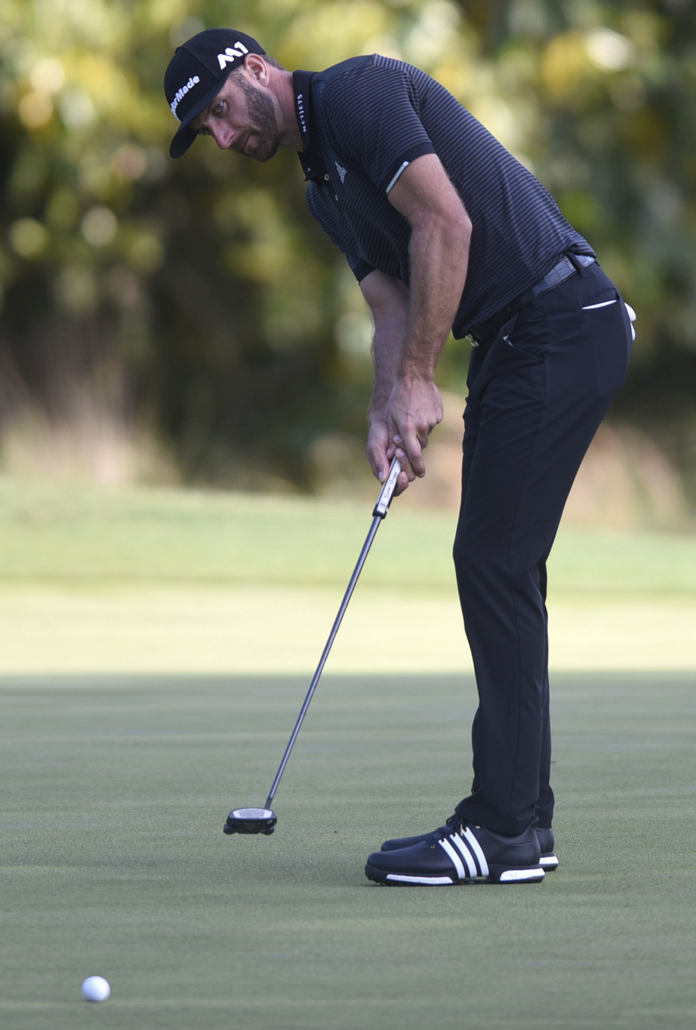 Dustin Johnson putts on the ninth green during the second round of the Wells Fargo Championship golf tournament at Eagle Point Golf Club in Wilmington, N.C., Friday, May 5, 2017. [Matt Born/The Star-News via AP)