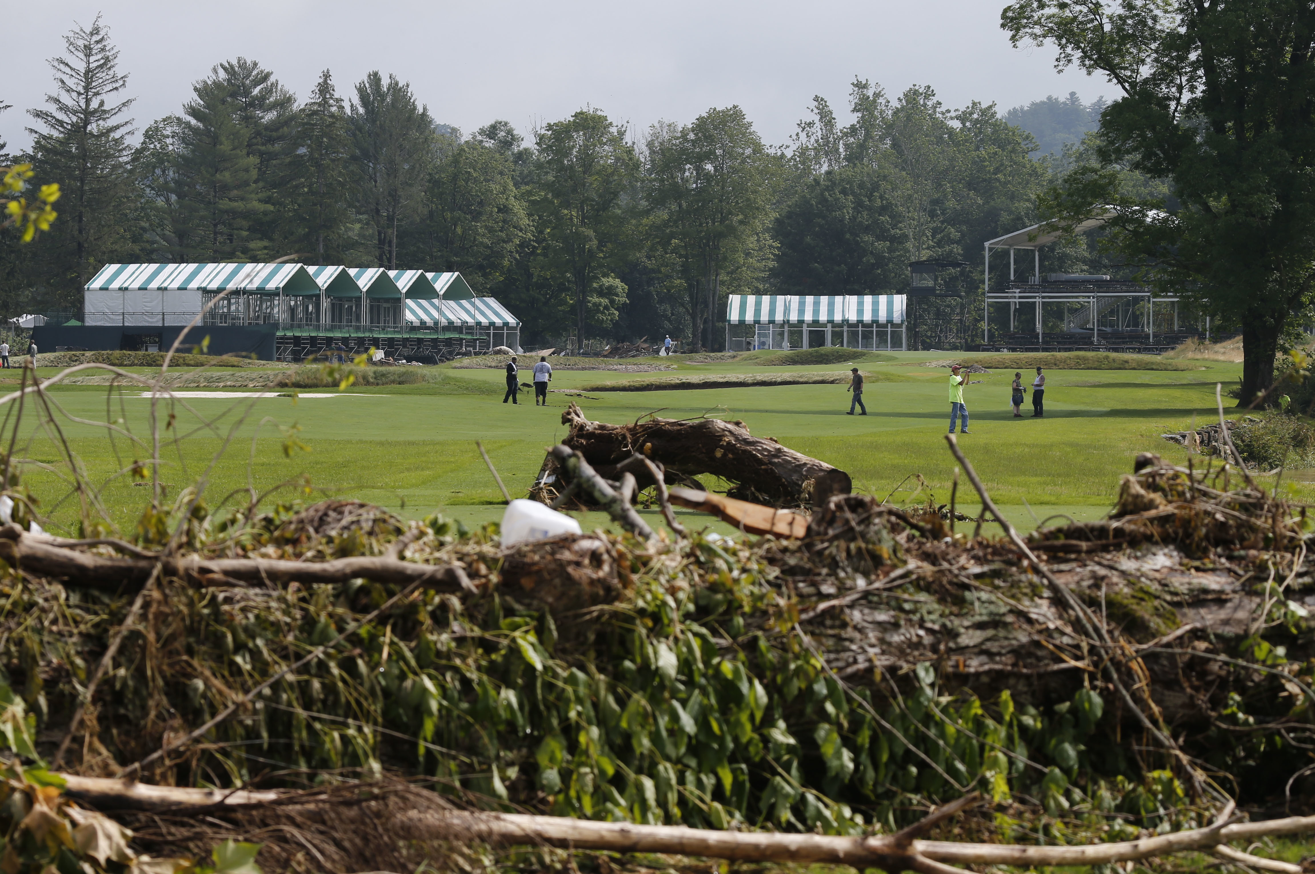 FILE - In this June 28, 2016, file photo, workers survey debris along the 17th fairway of the Old White Course on the property of the Greenbrier Resort in White Sulphur Springs, W. Va. Nearly a year since flooding from torrential rains left 23 people dead