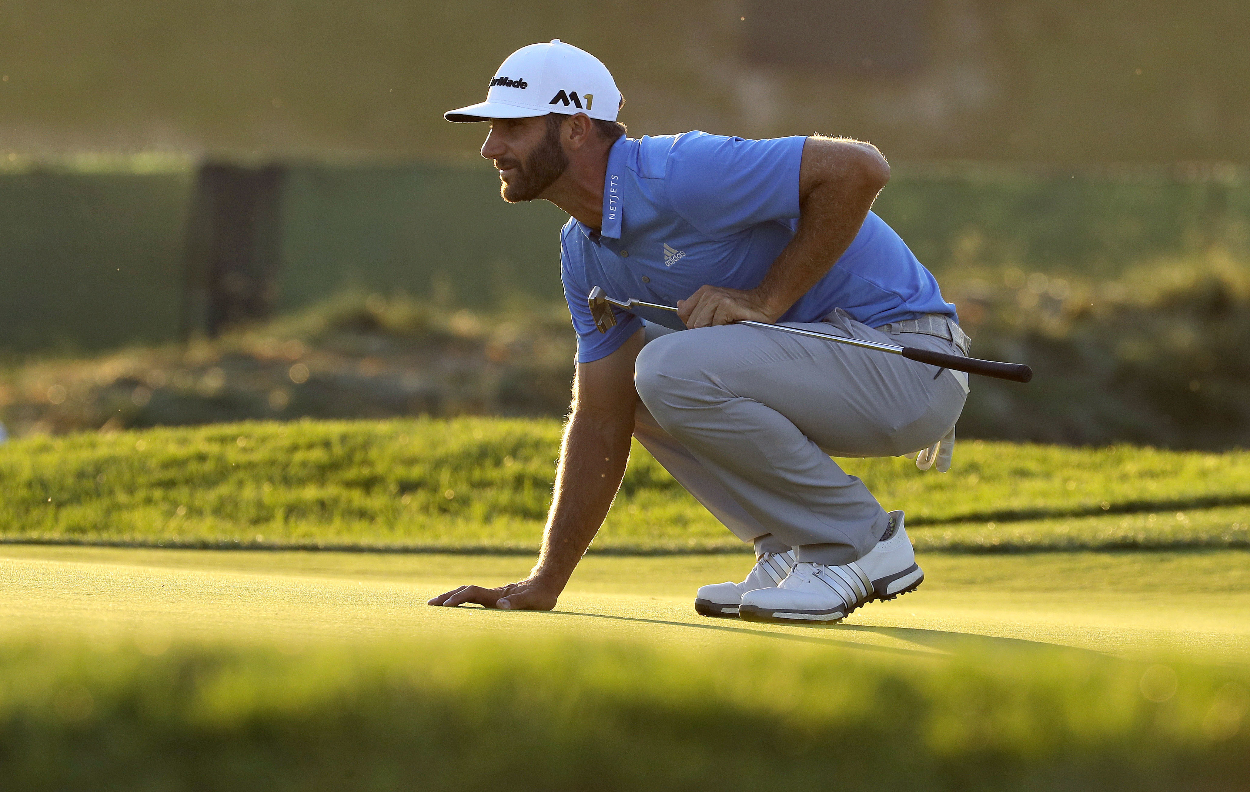FILE - In this June 17, 2016, file photo, Dustin Johnson lines up his putt on the seventh hole during the rain delayed second round of the U.S. Open golf championship at Oakmont Country Club, in Oakmont, Pa. Dustin Johnson had the perfect temperament to h