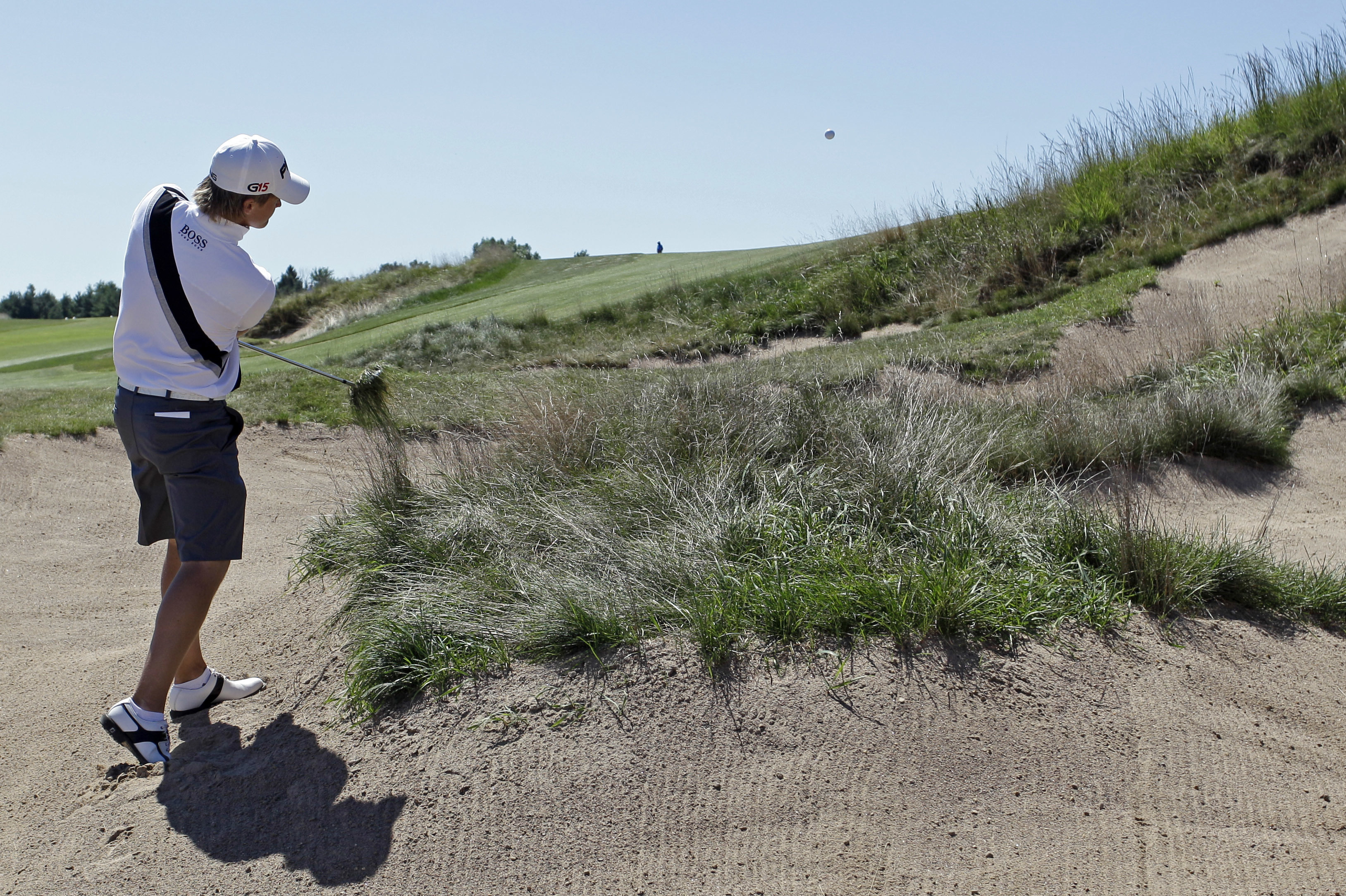 FILE - In this Aug. 25, 2011 file photo, Tom Lewis, of England, hits out of some rough in a trap on the first hole during the second round of match play at the U.S. Amateur golf tournament at Erin Hills Golf Course in Erin, Wis. The man who first imagined