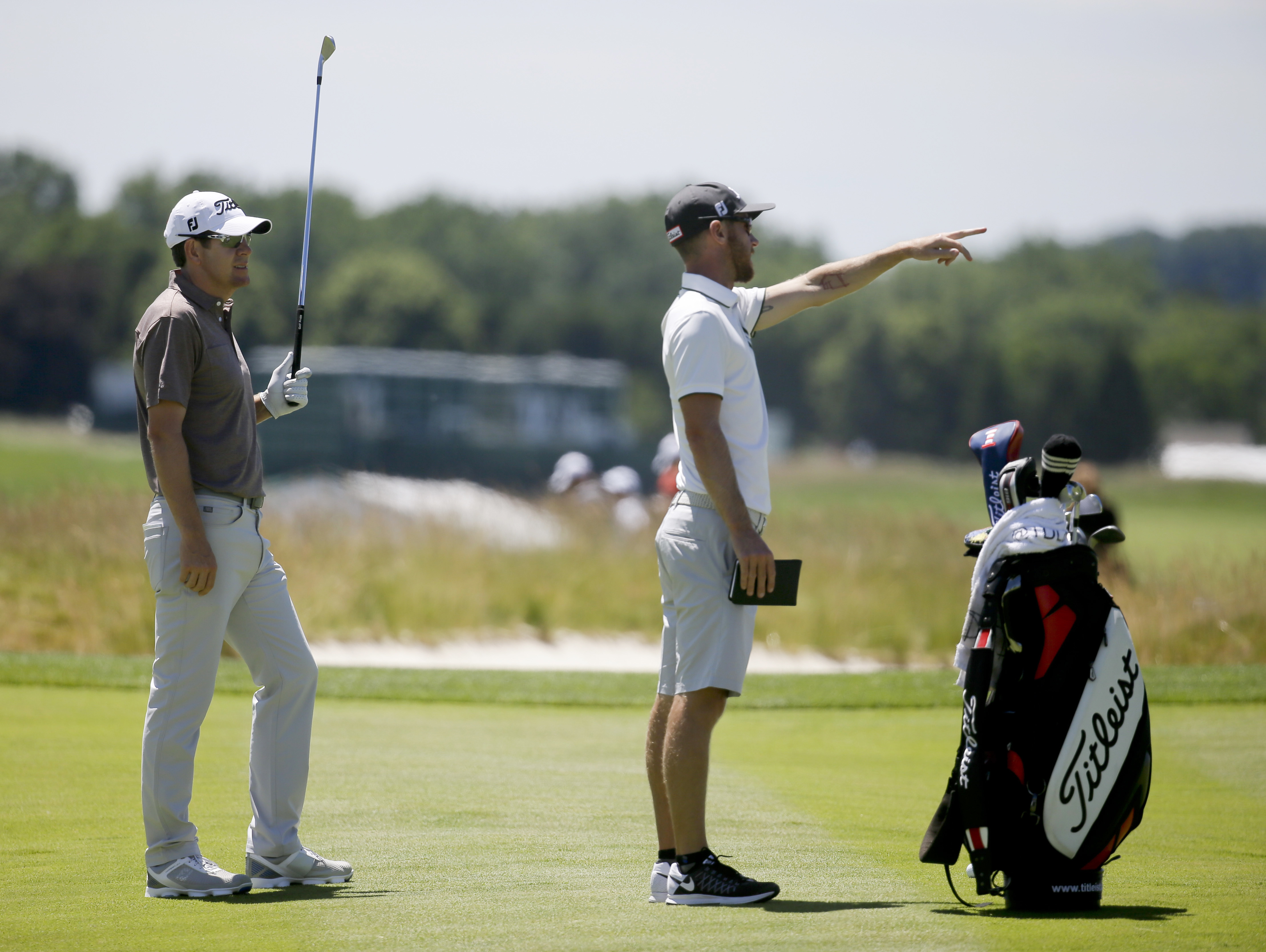 FILE - In this June 14, 2016, file photo, Aron Price, left, works with his caddie. Nick Flanagan, on the third hole during a practice round for the U.S. Open golf championship at Oakmont Country Club in Oakmont, Pa. For the second straight year, Aussies F