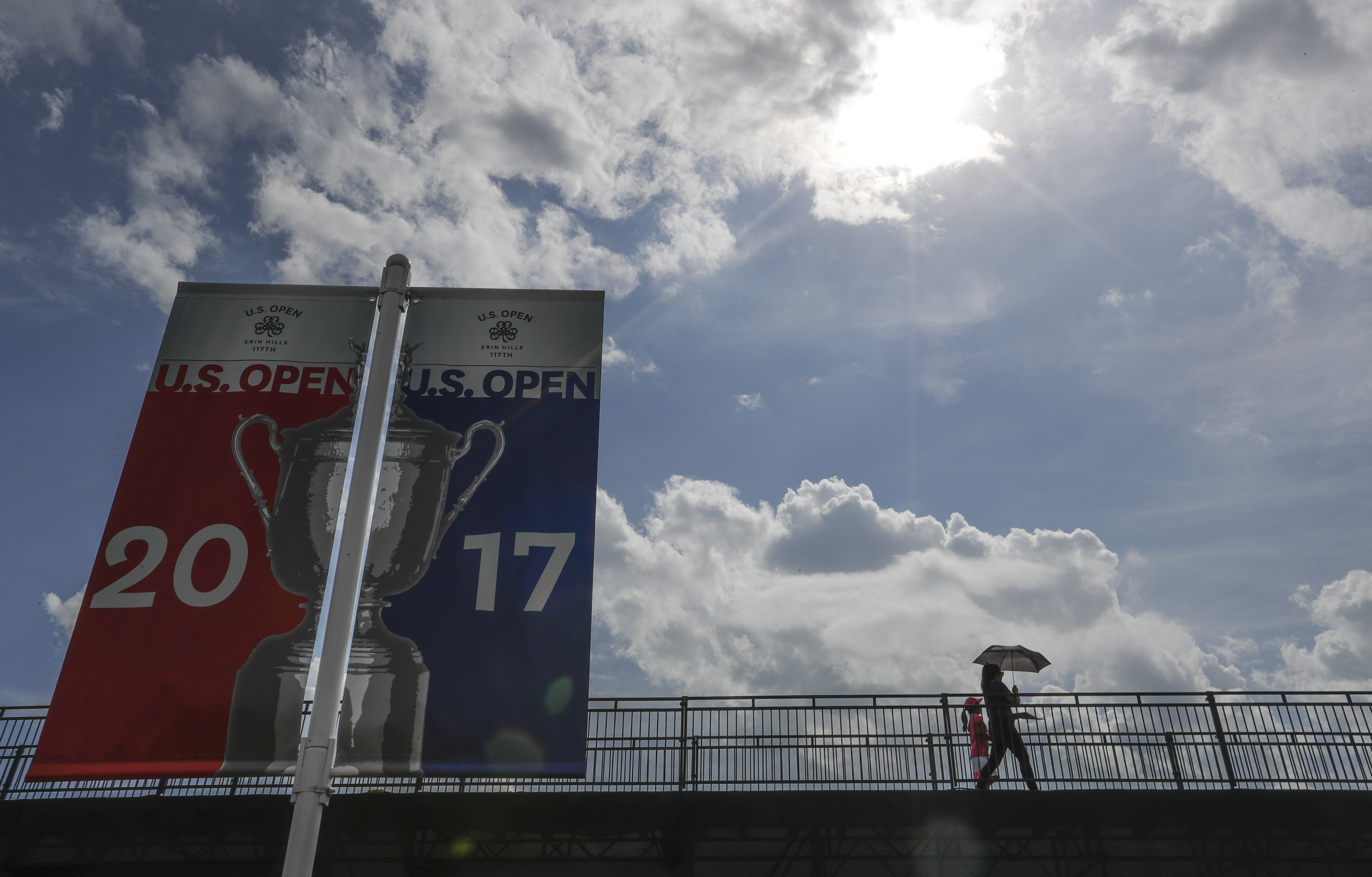 Fans walk on a bridges with an umbrella during a practice round for the U.S. Open golf tournament Wednesday, June 14, 2017, at Erin Hills in Erin, Wis. (AP Photo/Morry Gash)