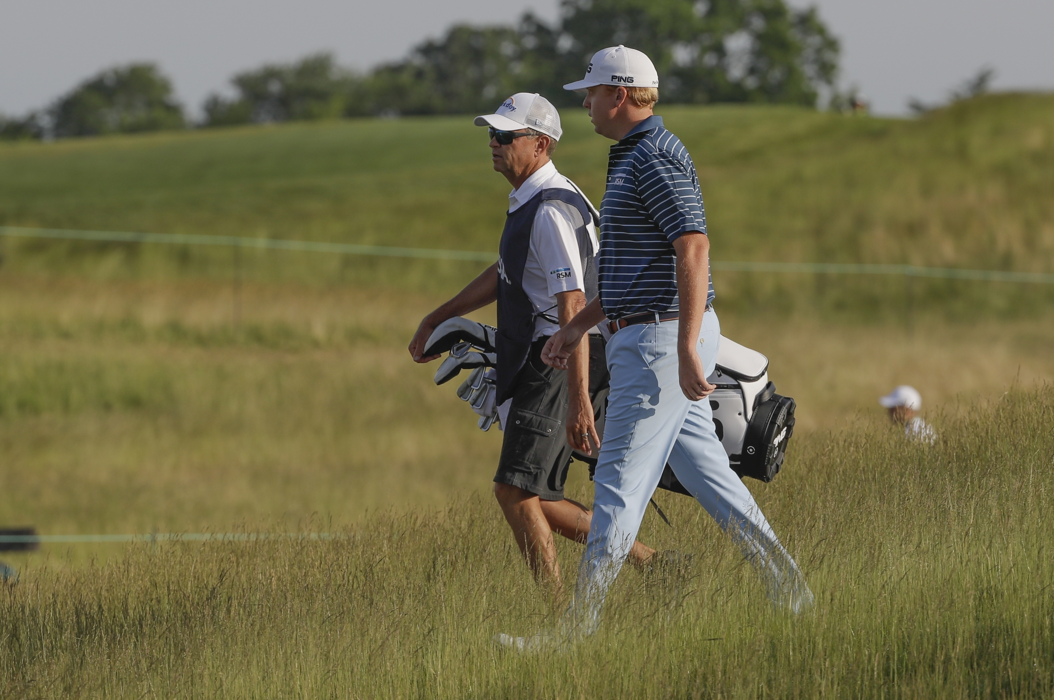 Davis Love IV with his father Davis Love III caddying walk up the first hole during the first round of the U.S. Open golf tournament Thursday, June 15, 2017, at Erin Hills in Erin, Wis. (AP Photo/David J. Phillip)