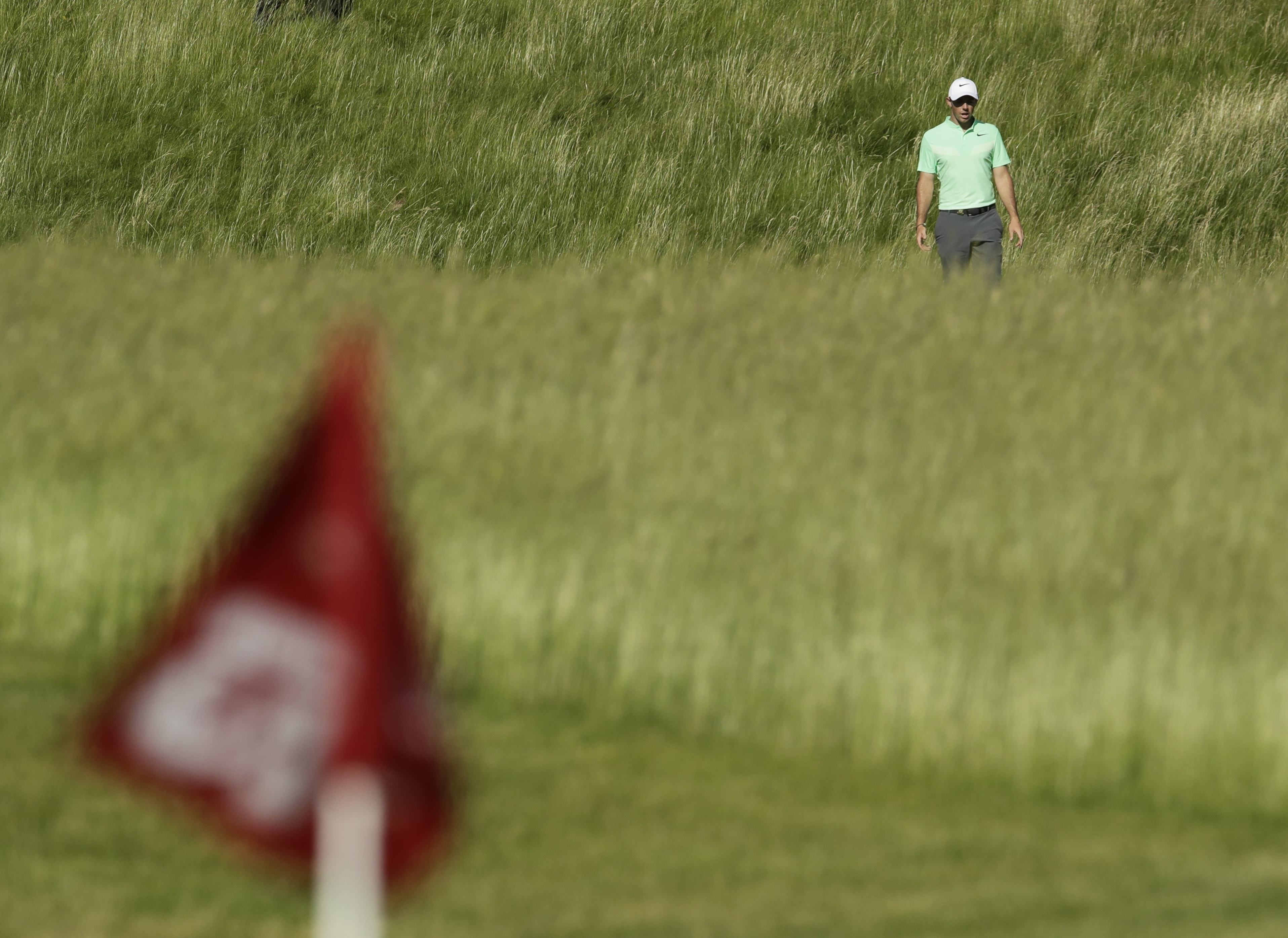 Rory Mcilroy, of Ireland, makes his way to the 12th hole during the first round of the U.S. Open golf tournament Thursday, June 15, 2017, at Erin Hills in Erin, Wis. (AP Photo/Charlie Riedel)