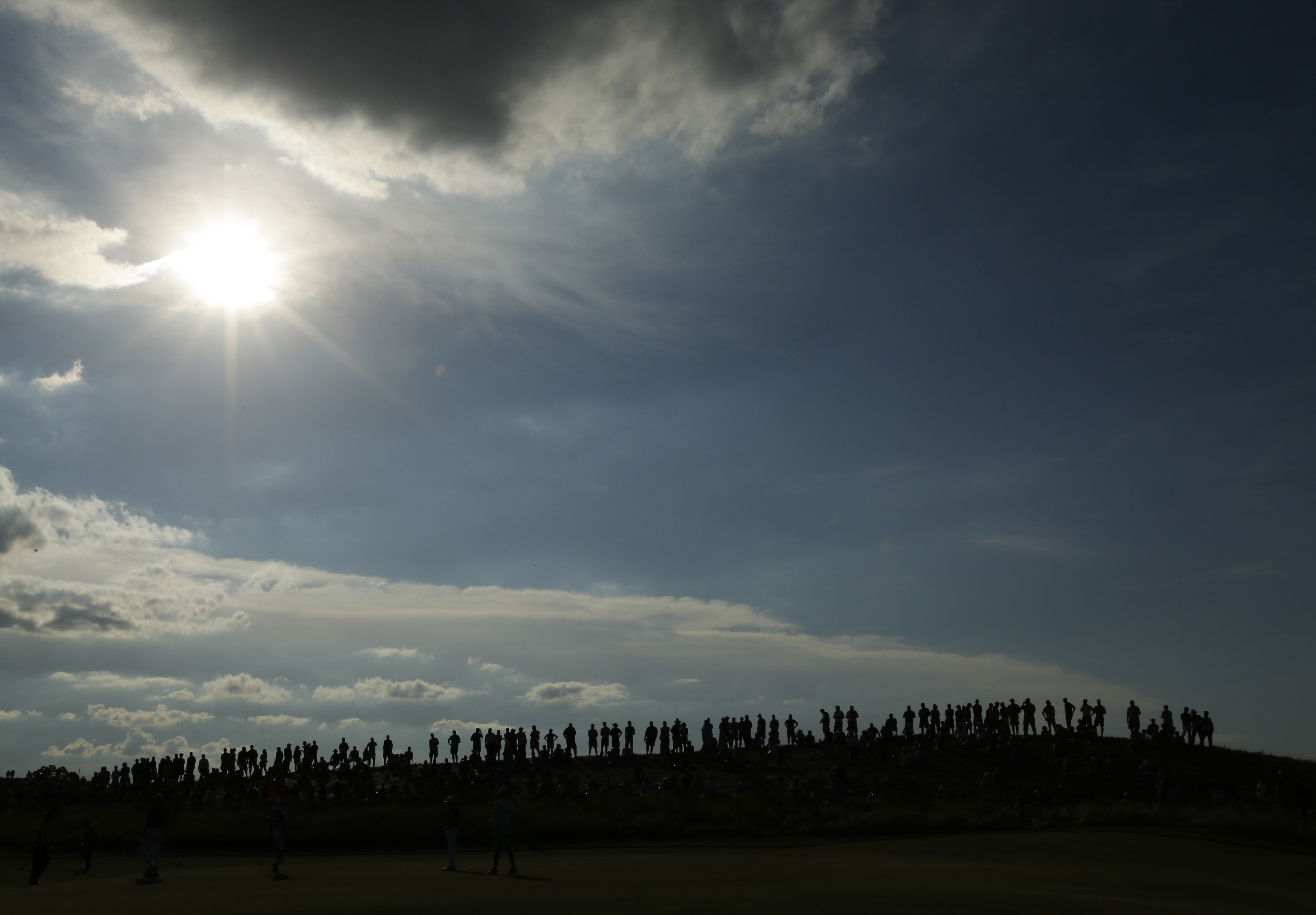 Fans line a hill on the 17th hole during the second round of the U.S. Open golf tournament Friday, June 16, 2017, at Erin Hills in Erin, Wis. (AP Photo/Charlie Riedel)